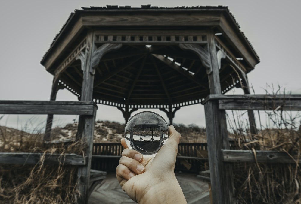person holding ball in front of gazebo