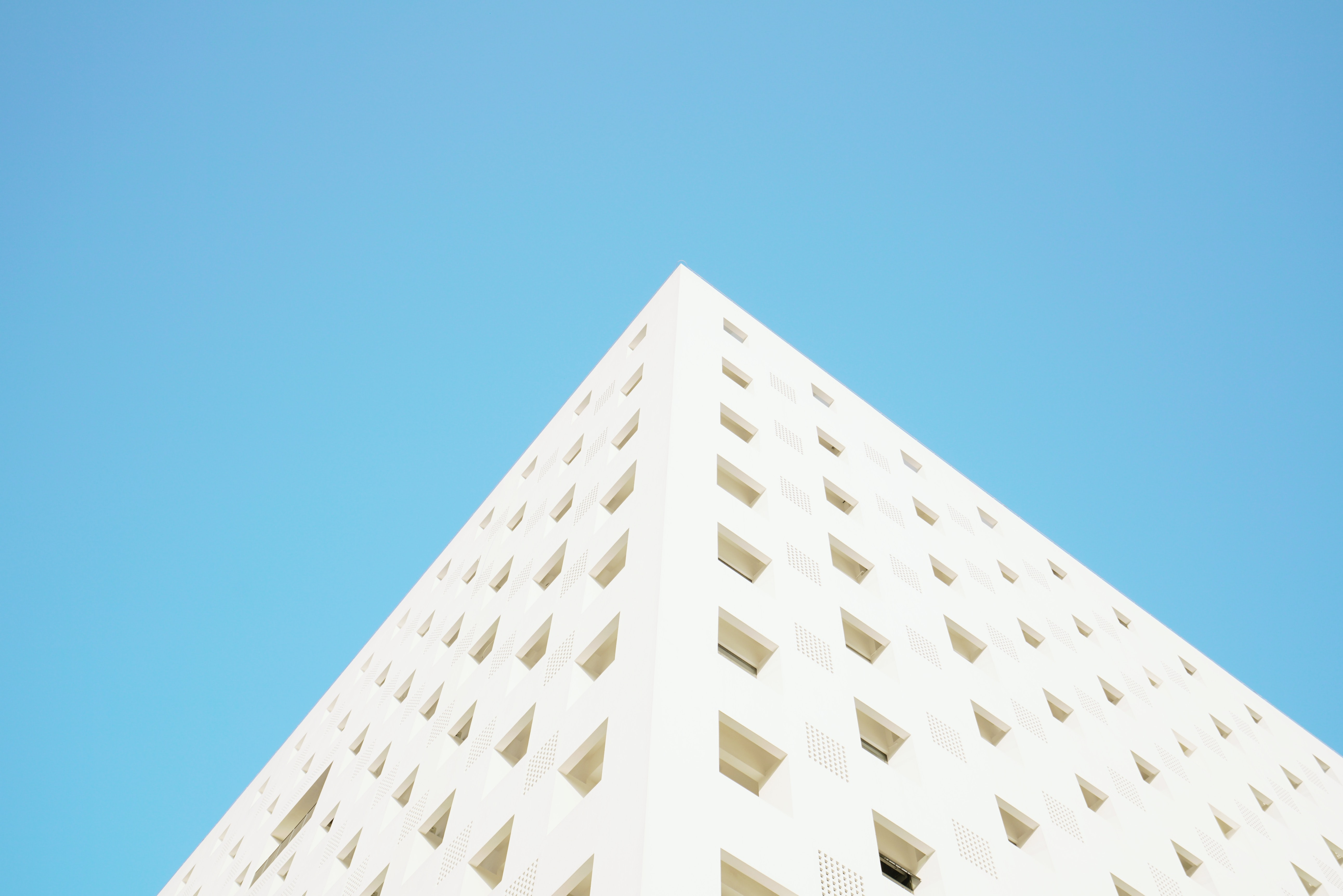 worm's eye view photography of white building under blue clear sky during daytime