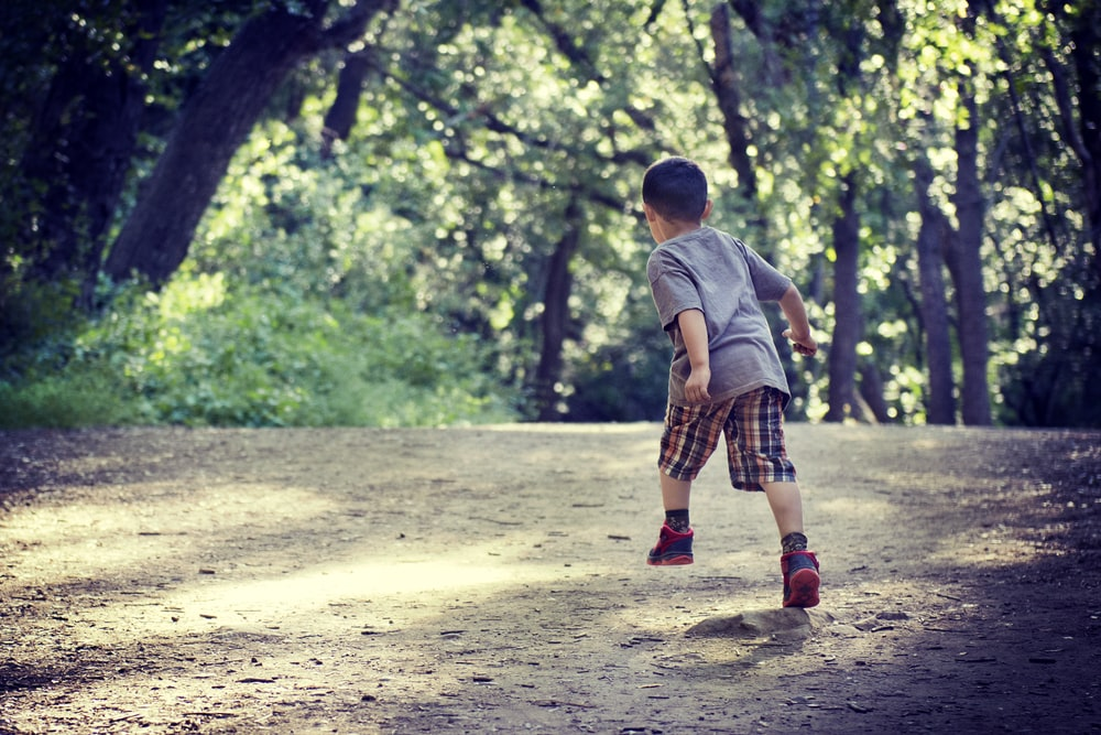 boy hopping on sand