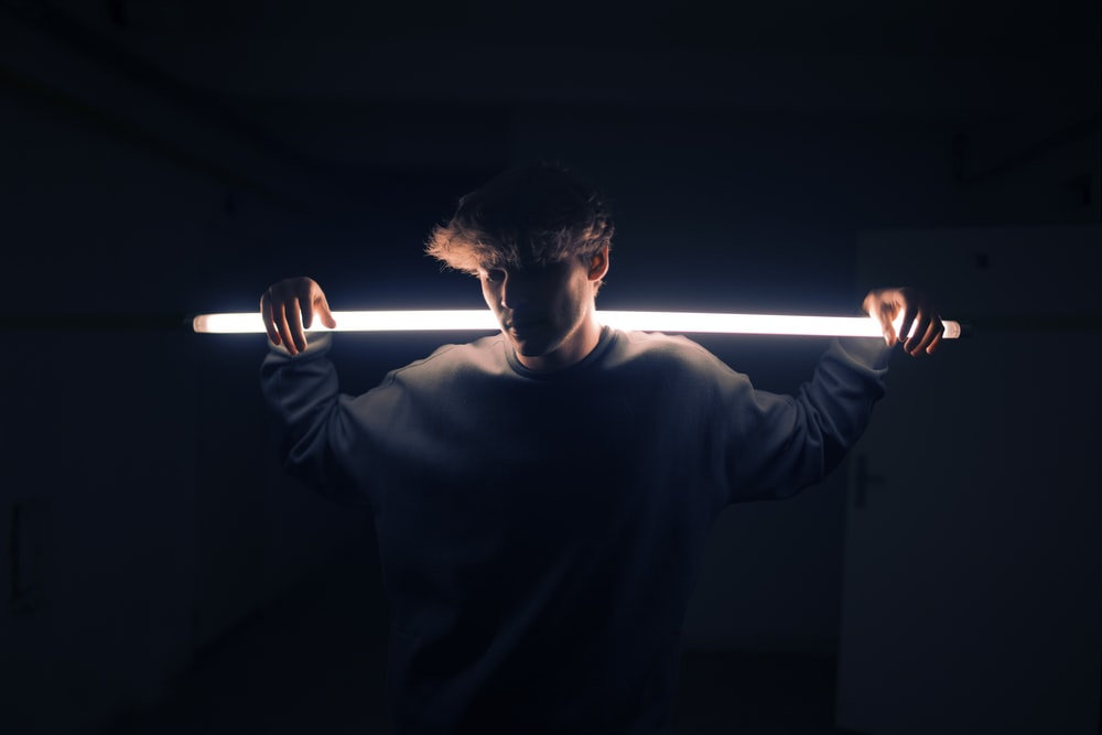 low light photography of man in gray sweatshirt
