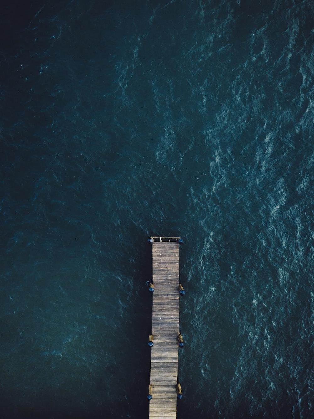 brown wooden bridge on body of water