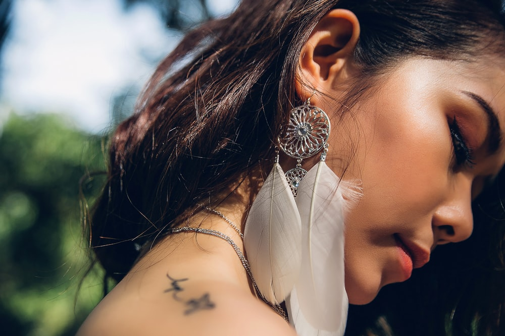 selective focus photo of woman wearing silver-colored and white feather earring