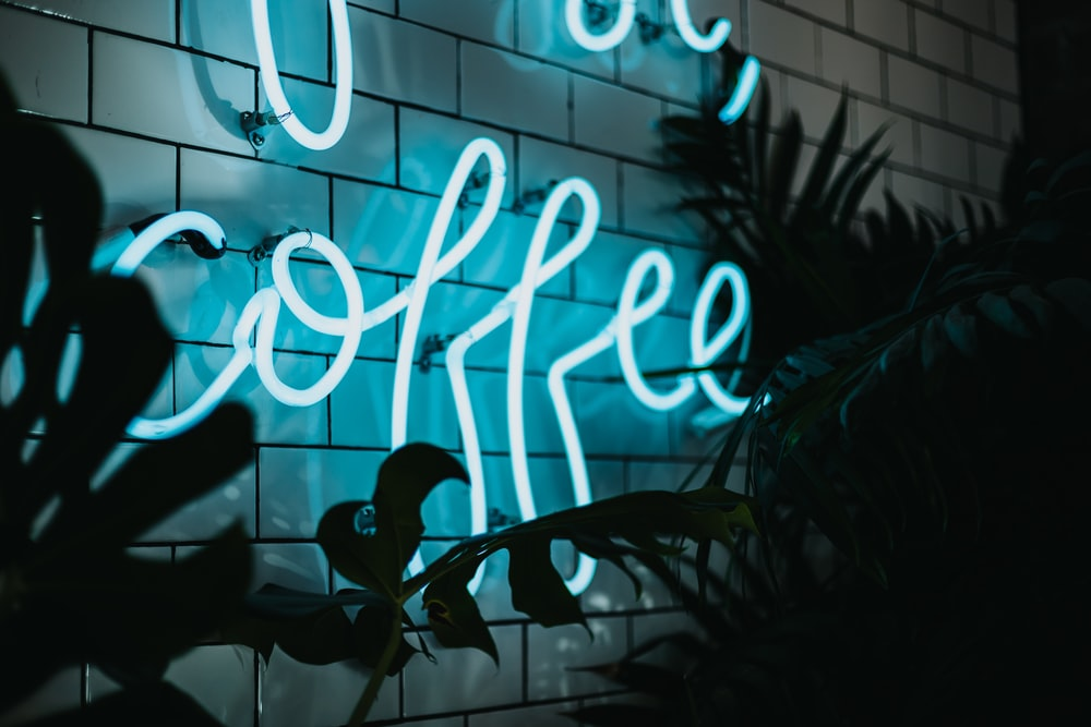 Coffee neon signage turned on near plant