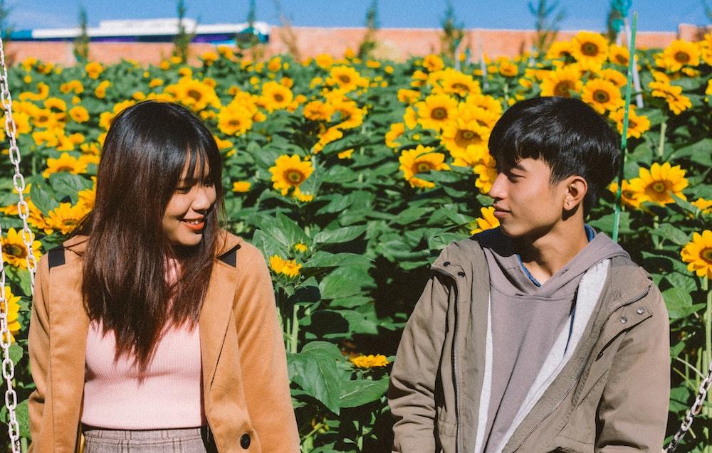 couple sitting beside sunflower field