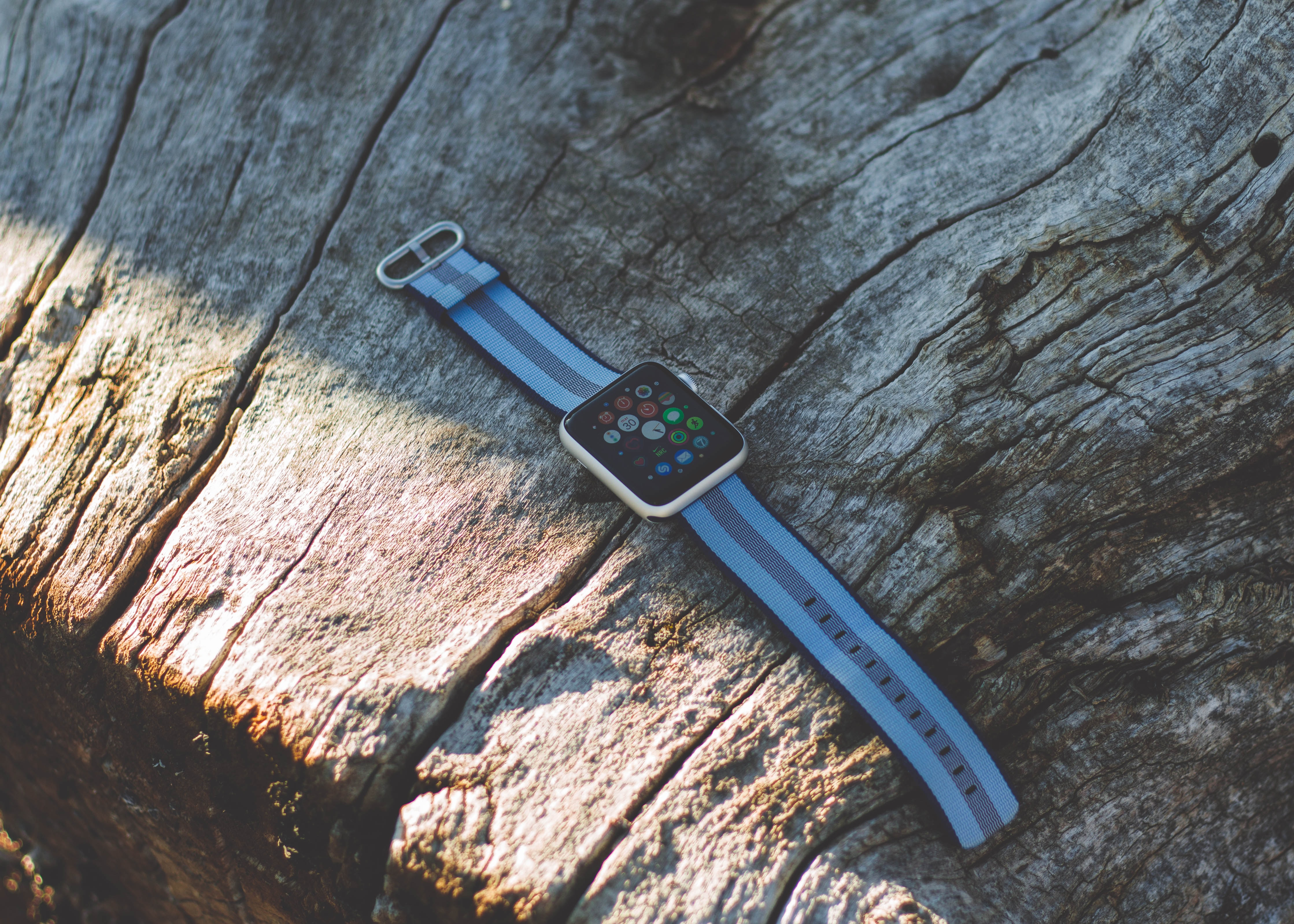 white Apple watch on bron wooden surface