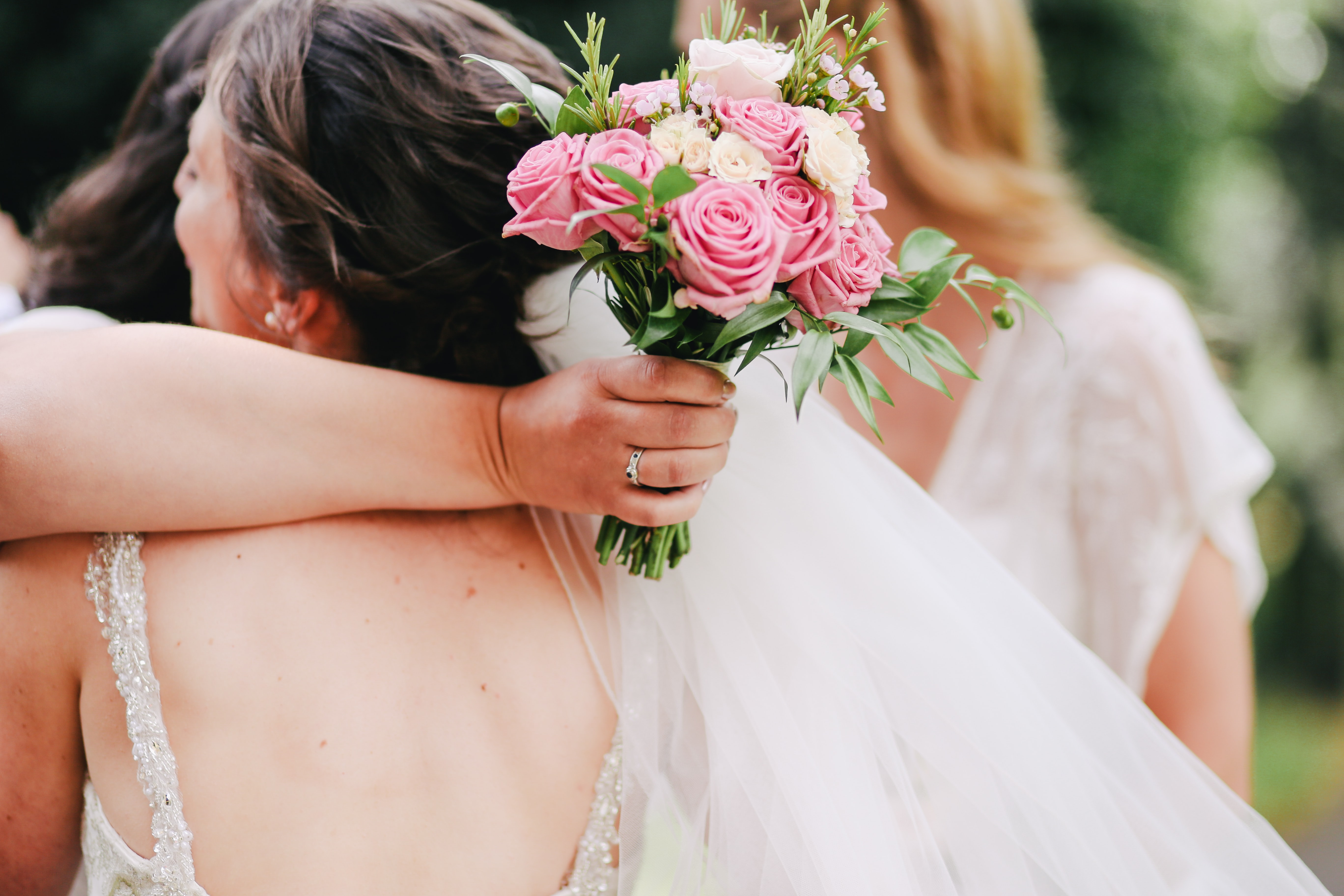 woman hugging another woman while holding bouquet of pink roses
