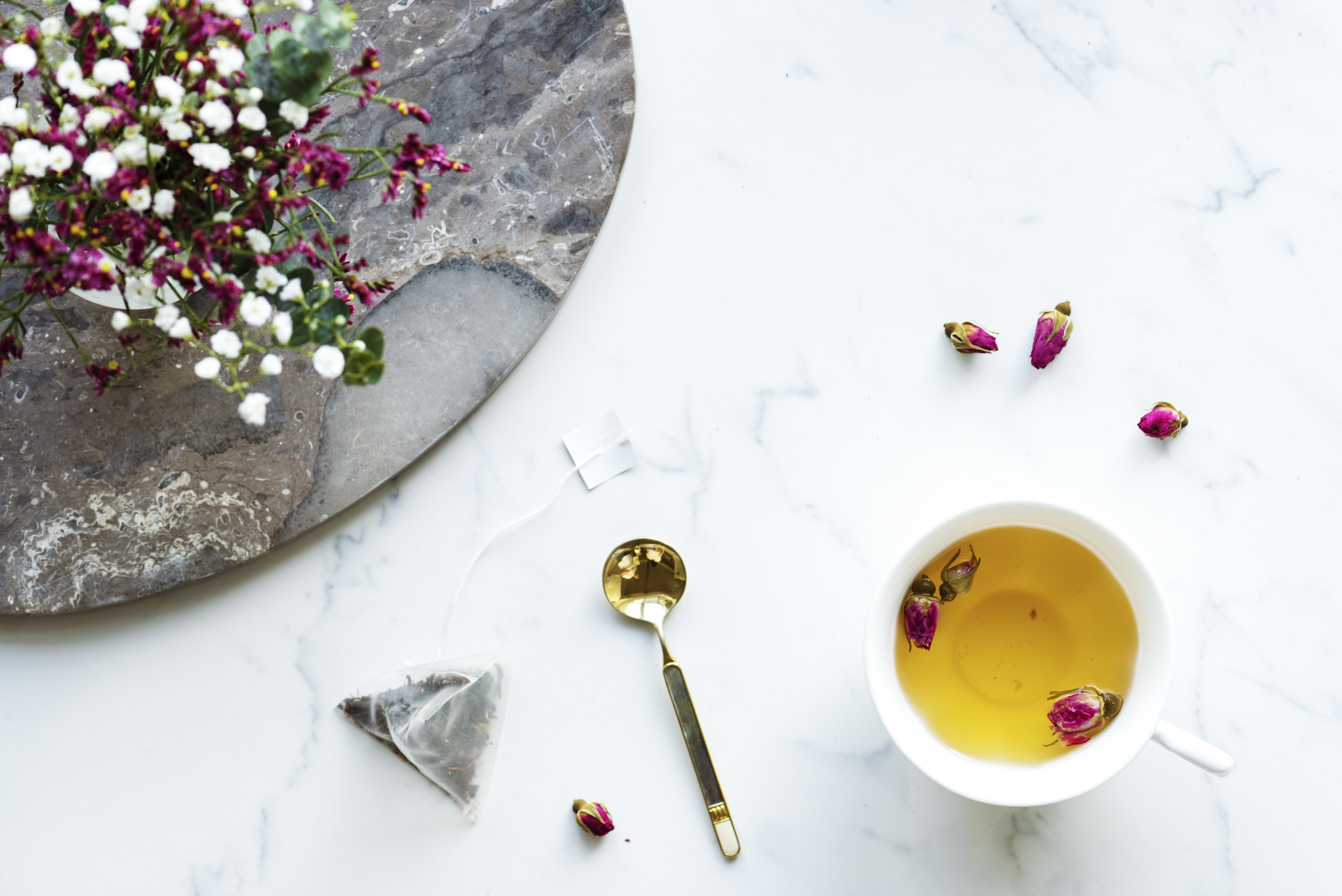 white ceramic teacup near gold-colored spoon