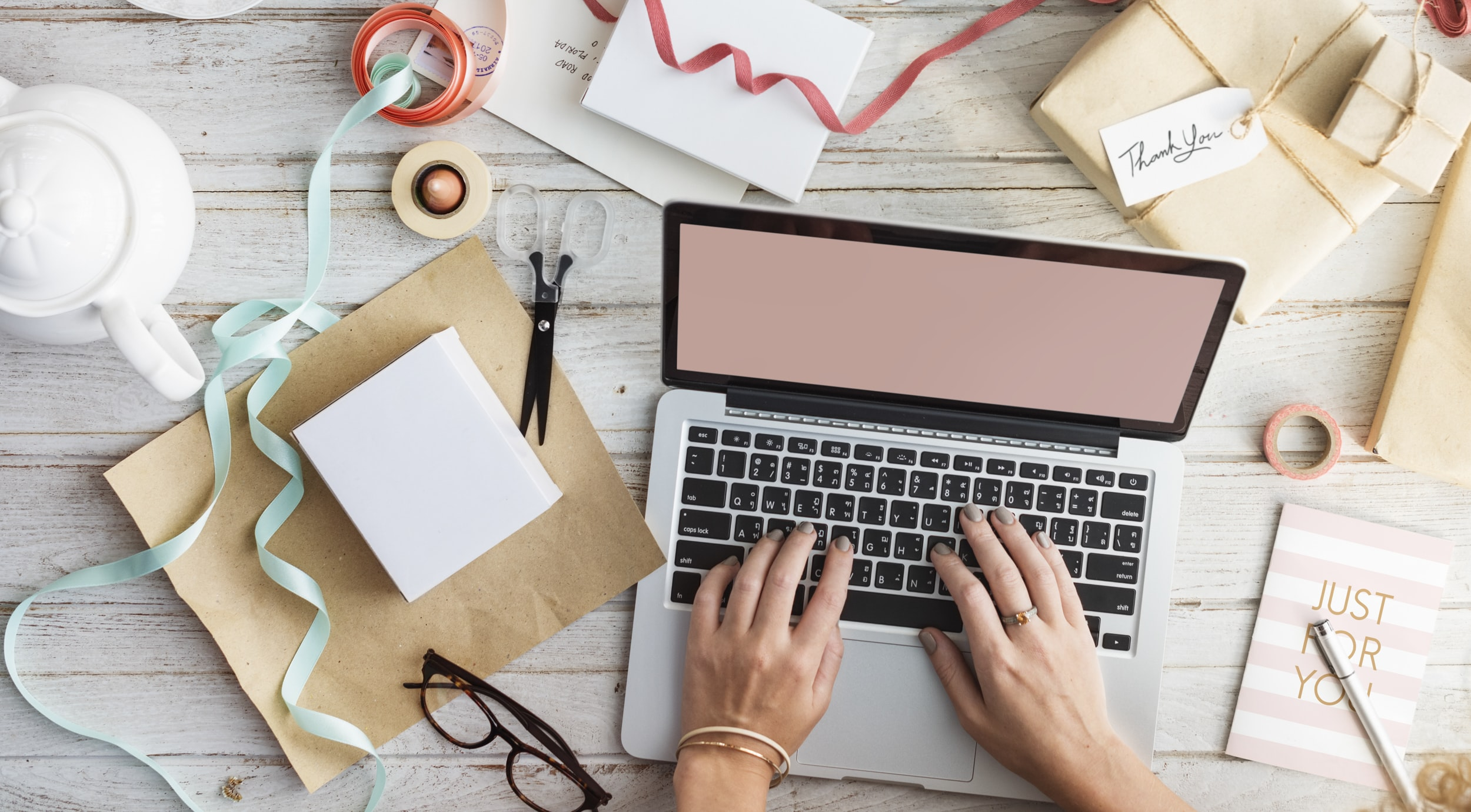 person typing on MacBook Pro beside eyeglasses