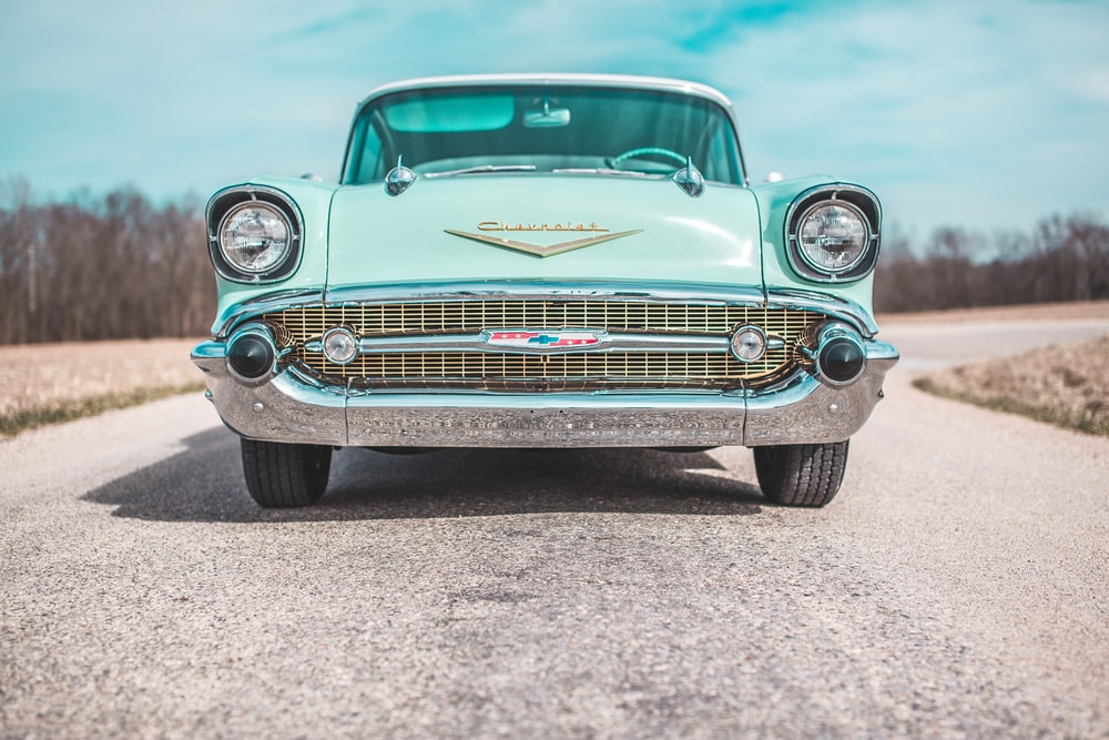 low-angle photo of classic teal Chevrolet car