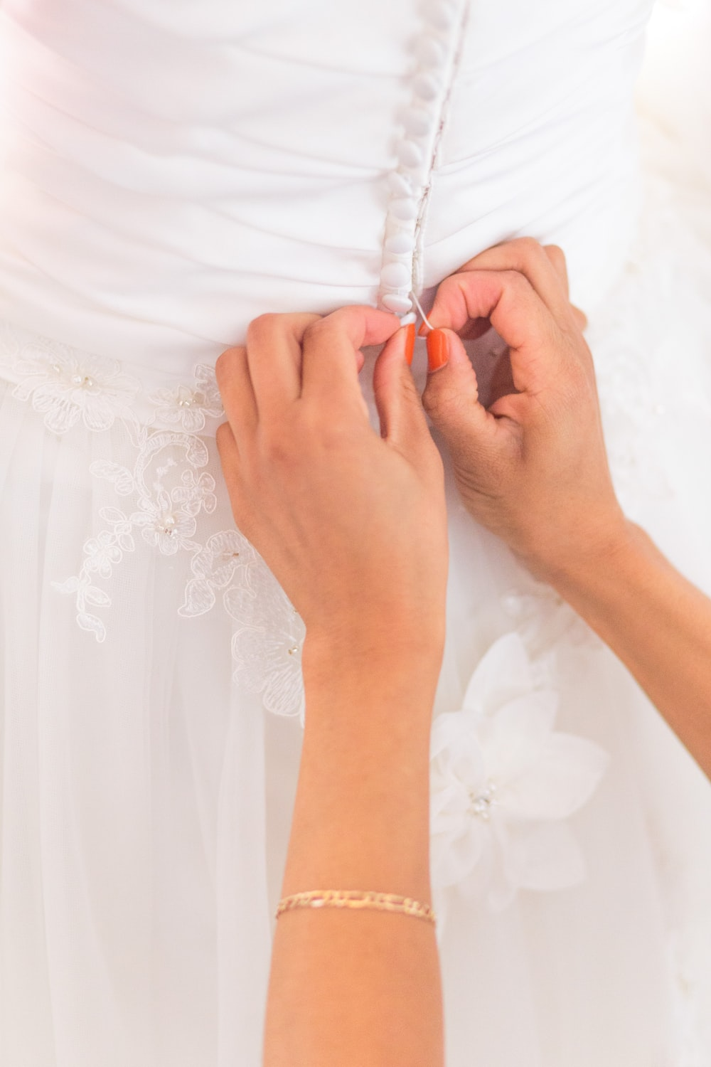 person holding white floral dress
