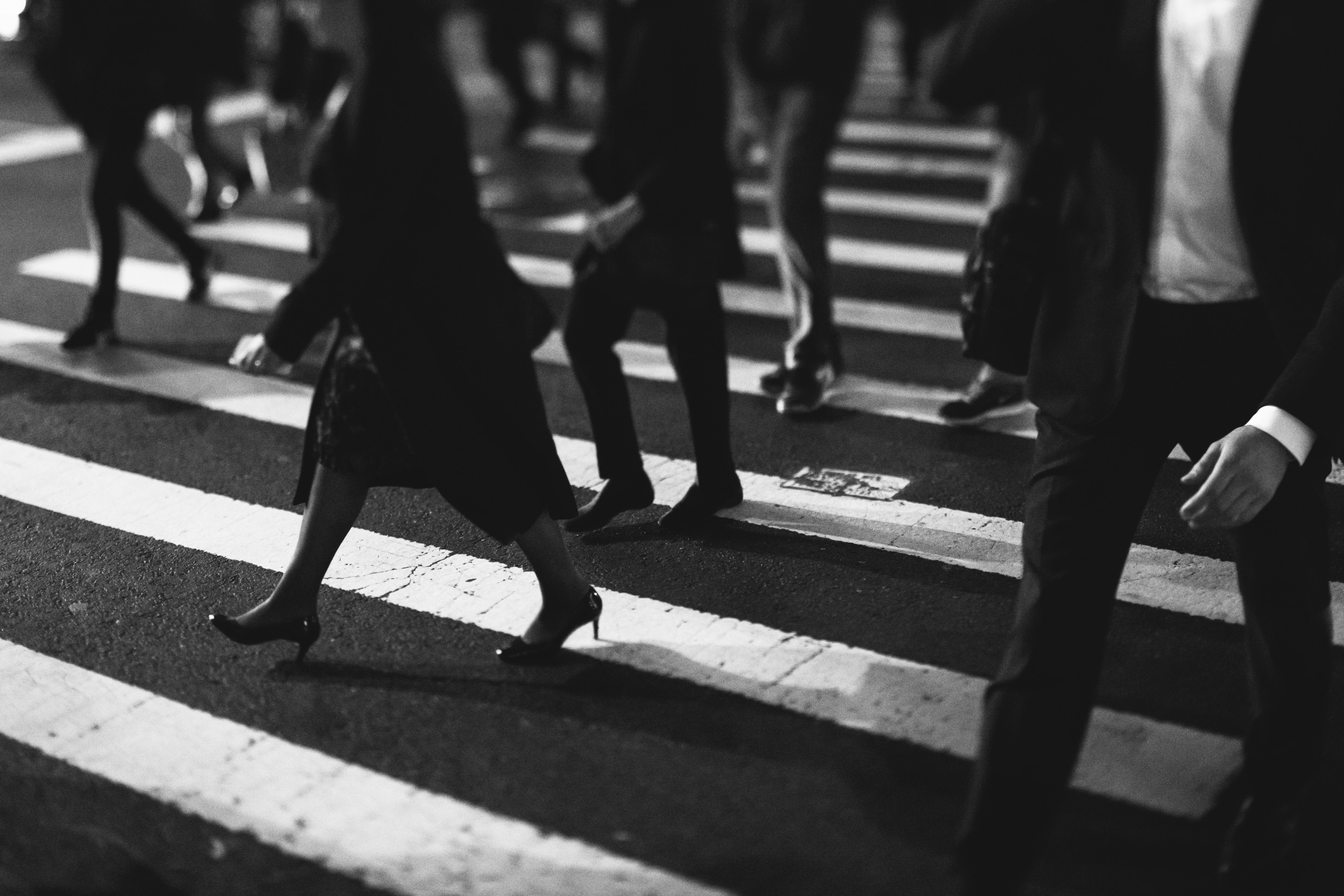 grayscale photo of group of people passing on pedestrian lane