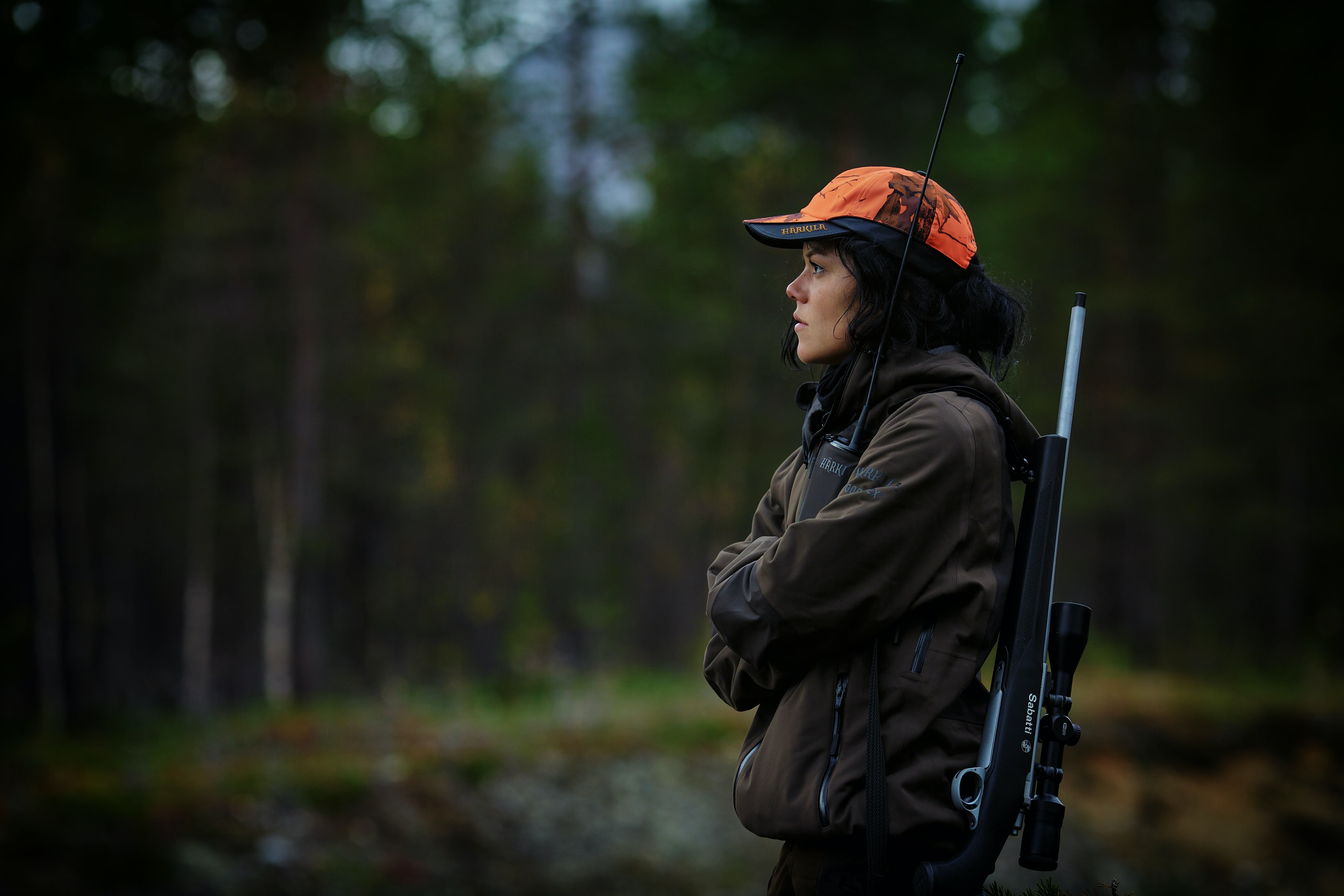 woman carrying hunting rifle in woods