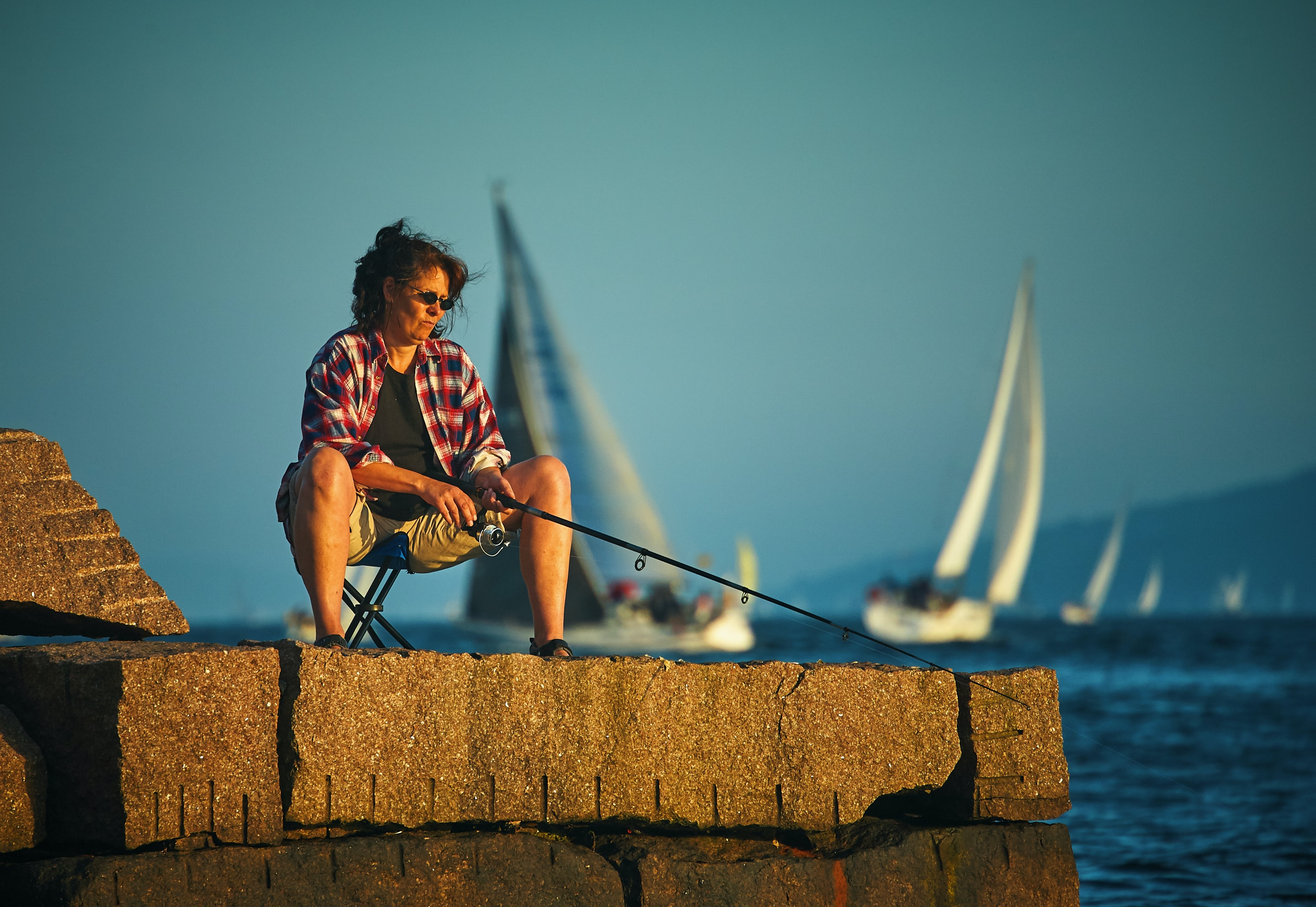 woman sitting down holding black fishing rod waiting for fish