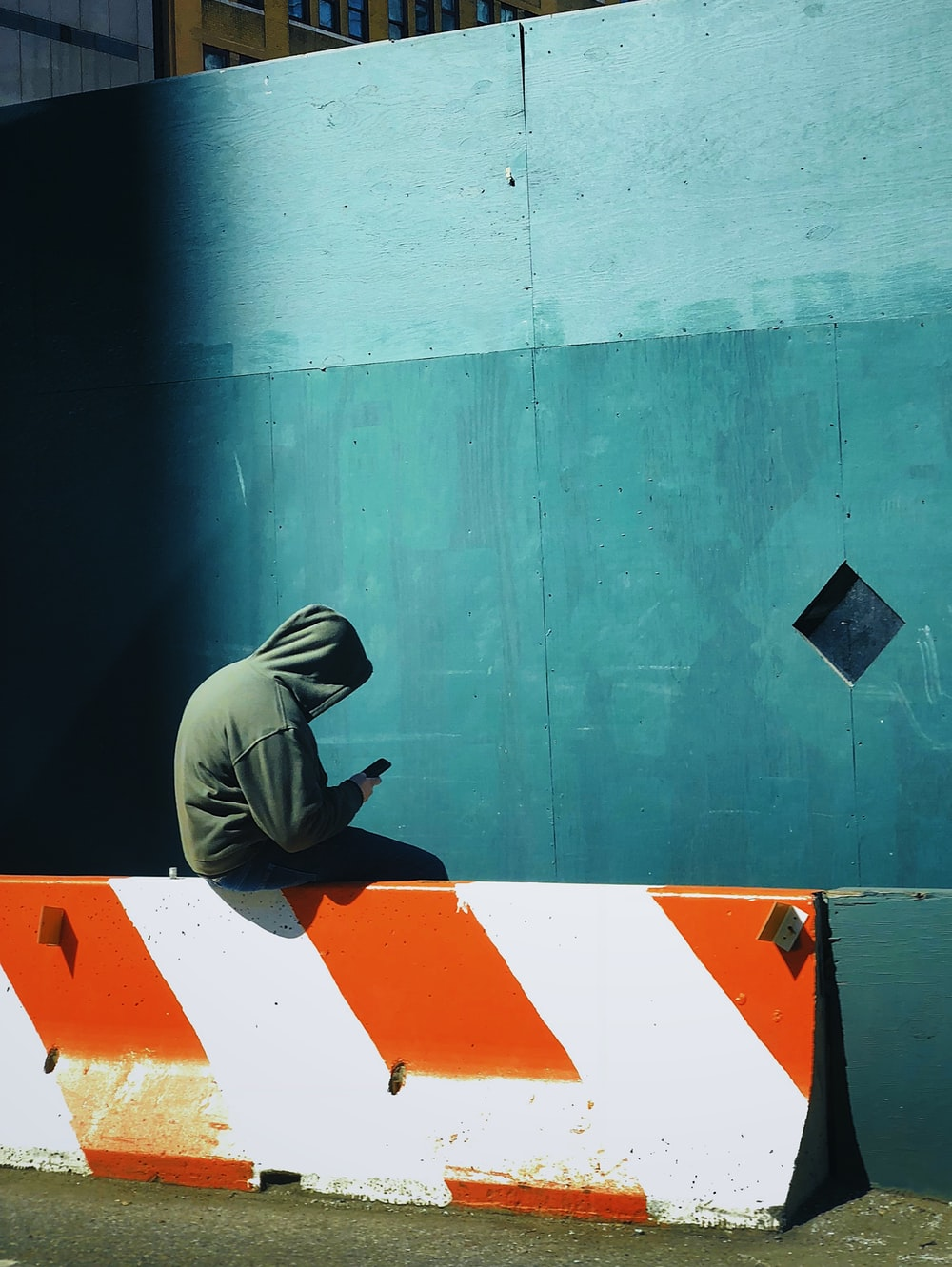 person in hooded jacket using smartphone