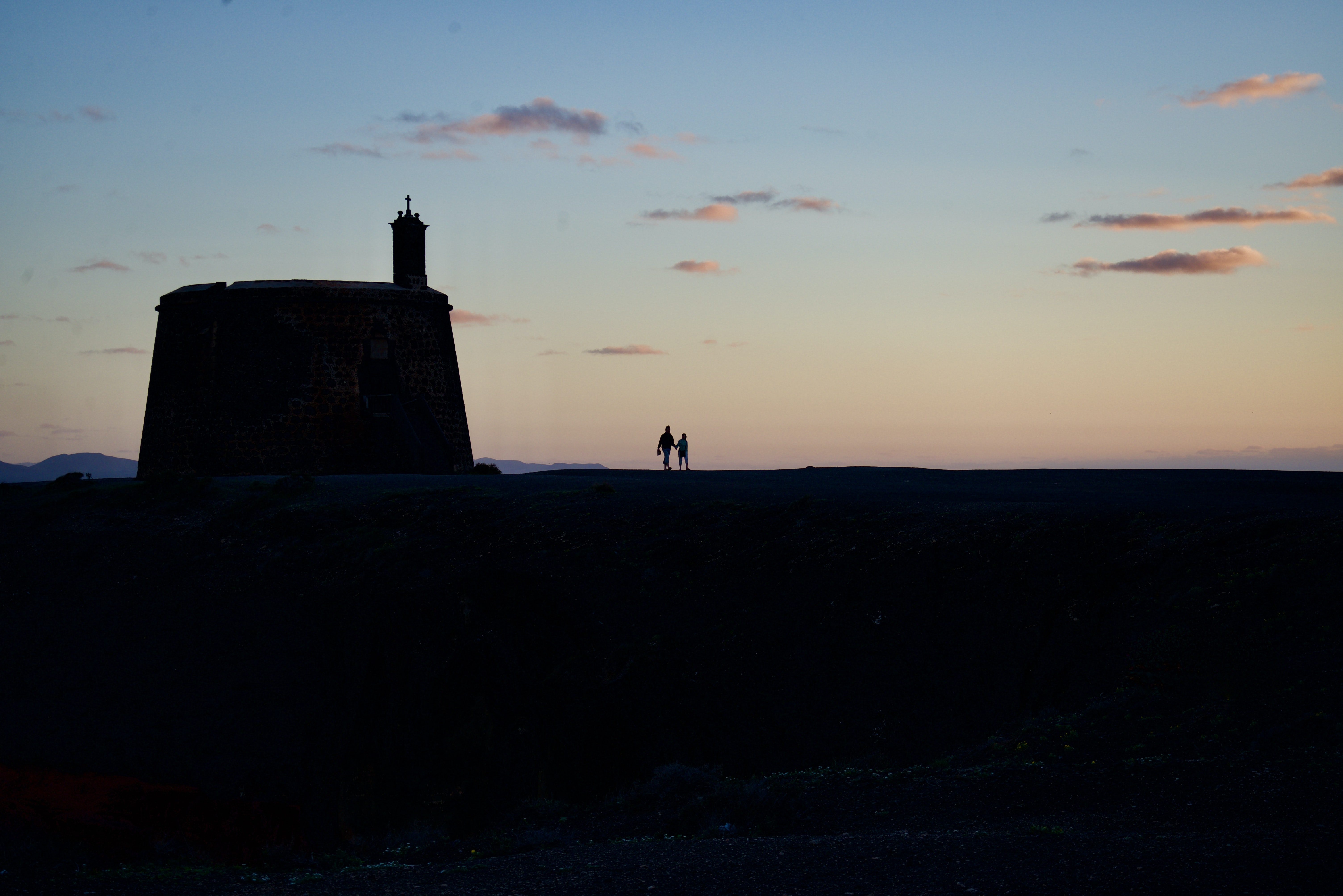 two people standing near structure silhouette photography