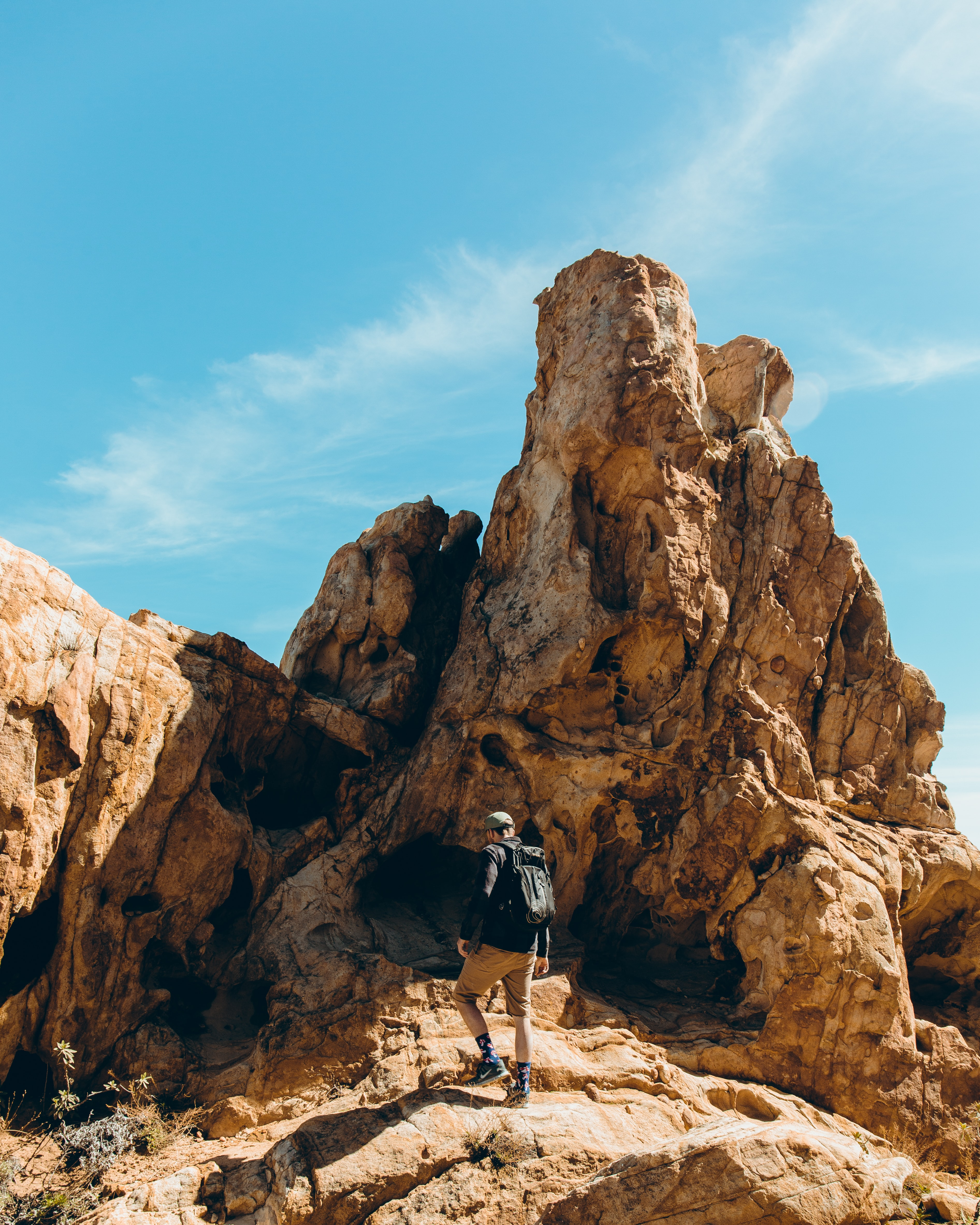 man standing in front of rock formation