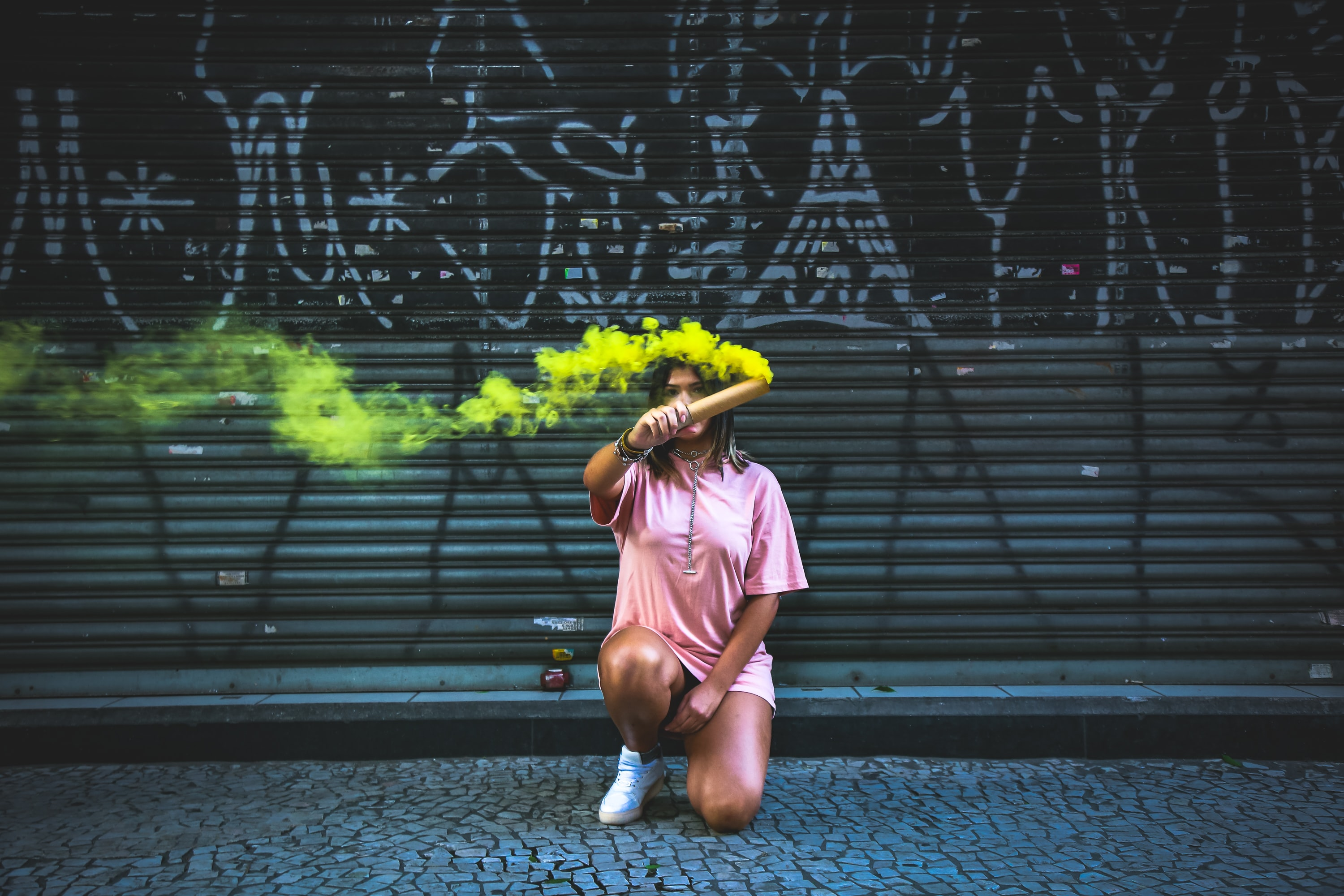 woman holding green smoke signage
