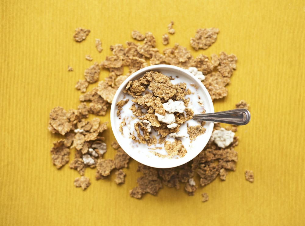 top view of corn flakes in bowl with milk and silver spoon