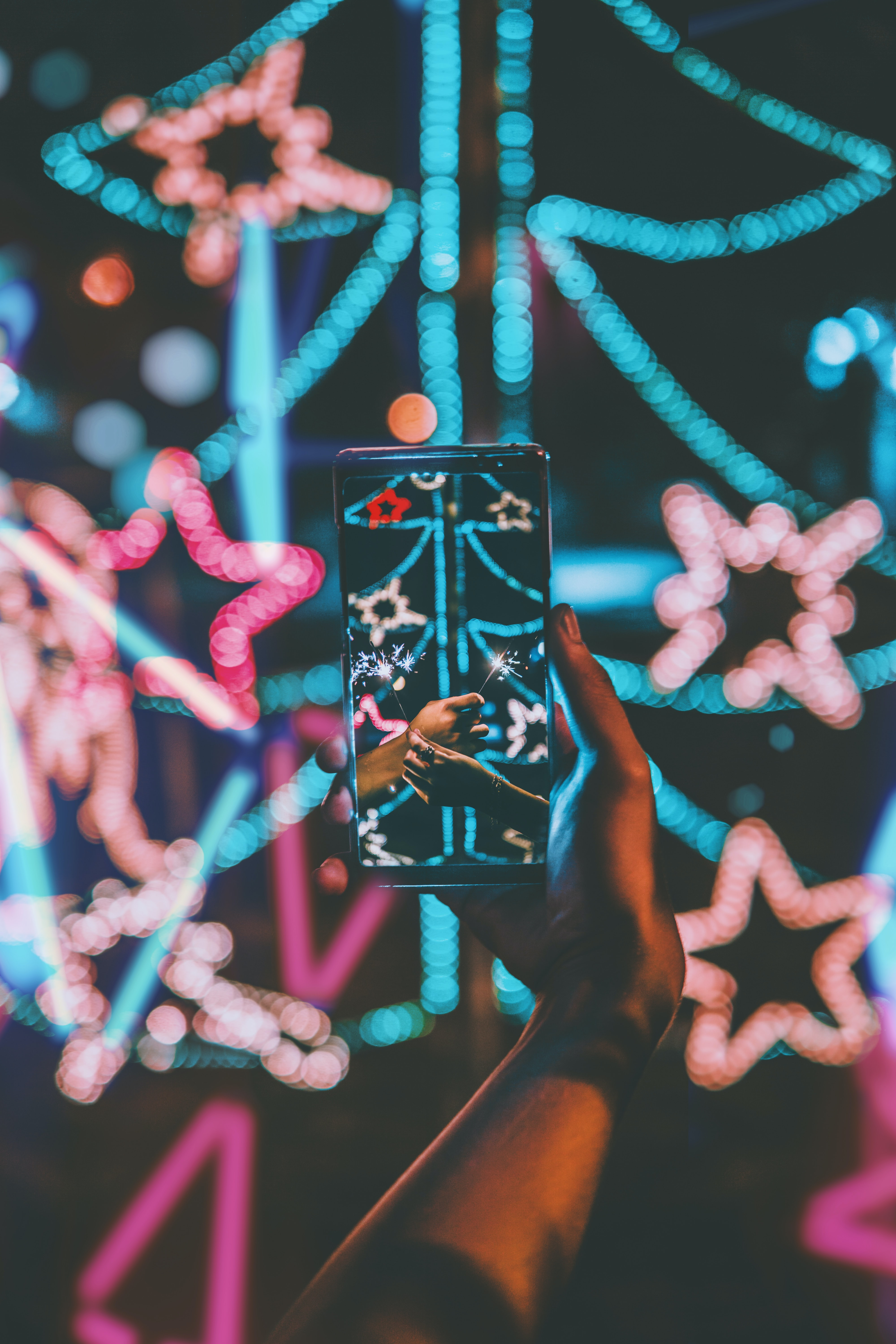 bokeh photography of person holding Android smartphone