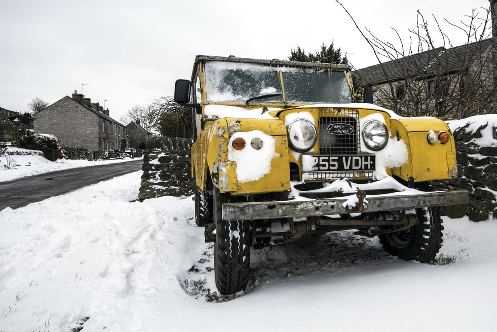 yellow truck on snow covered road