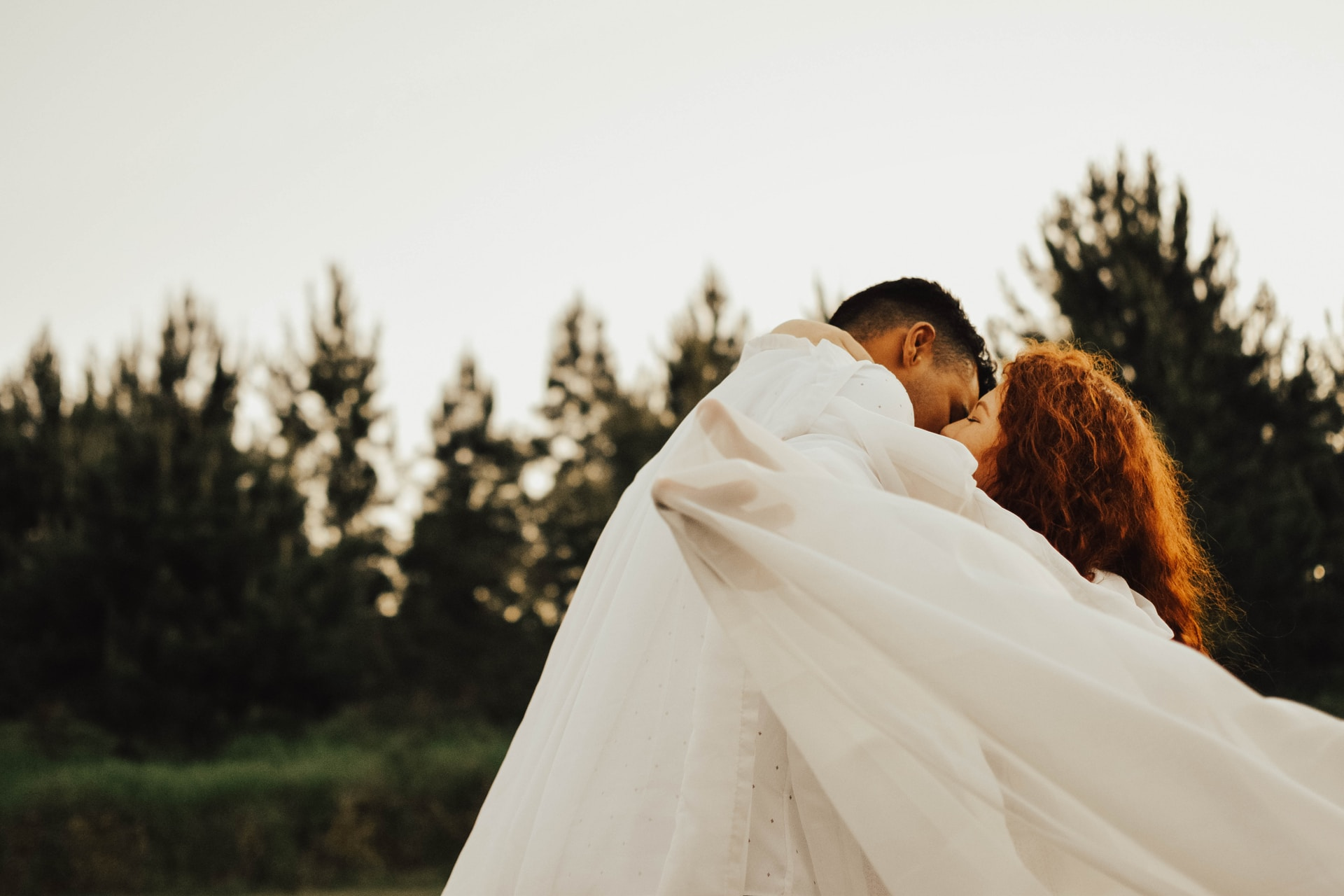man kissing woman in fabric during daytime