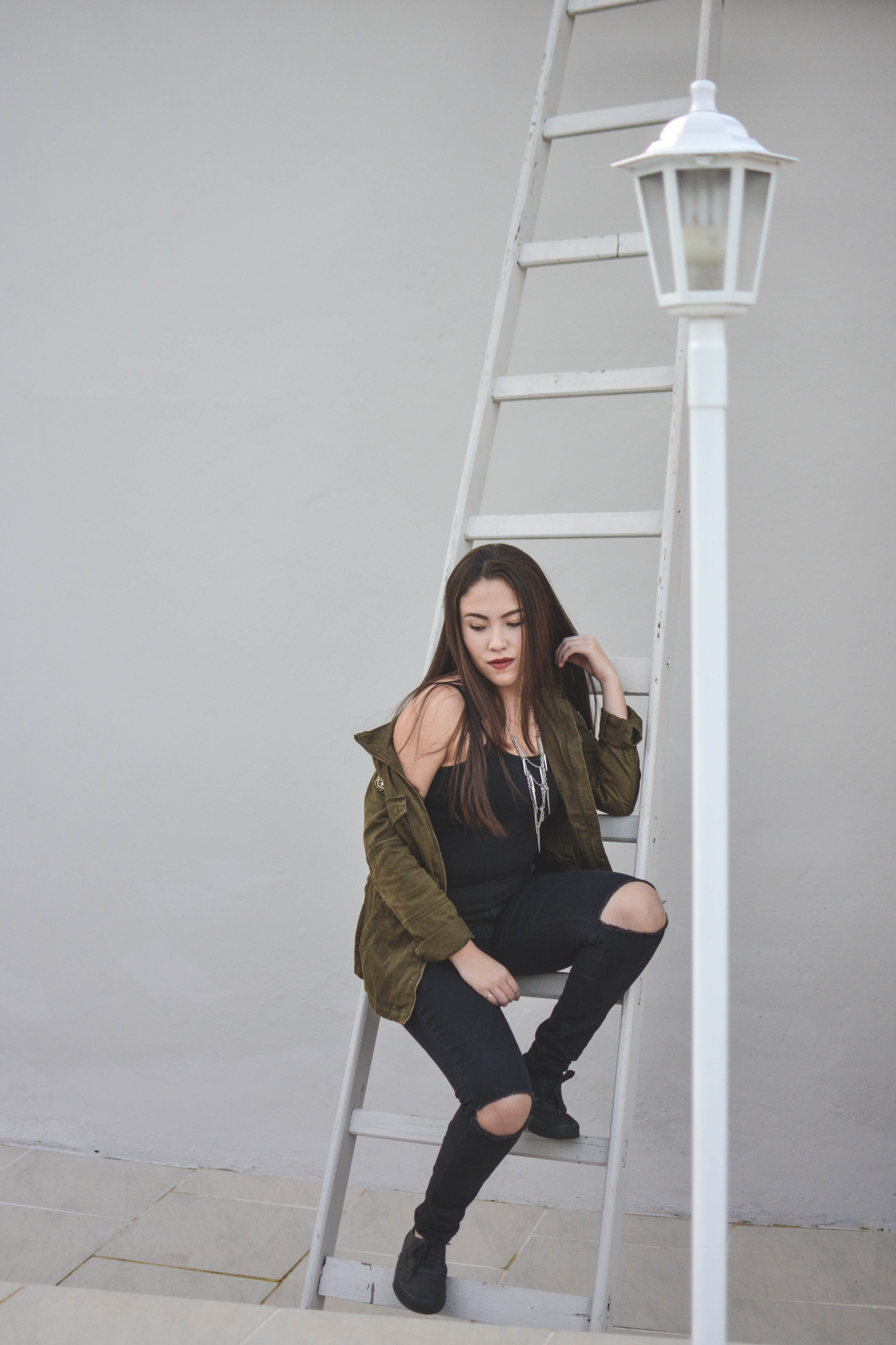 woman sitting on white steel ladder