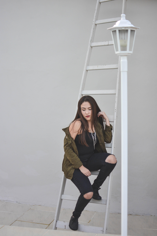 woman sitting on white steel ladder