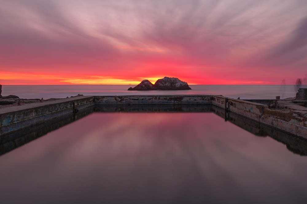 landscape photography of rock formation on body of water