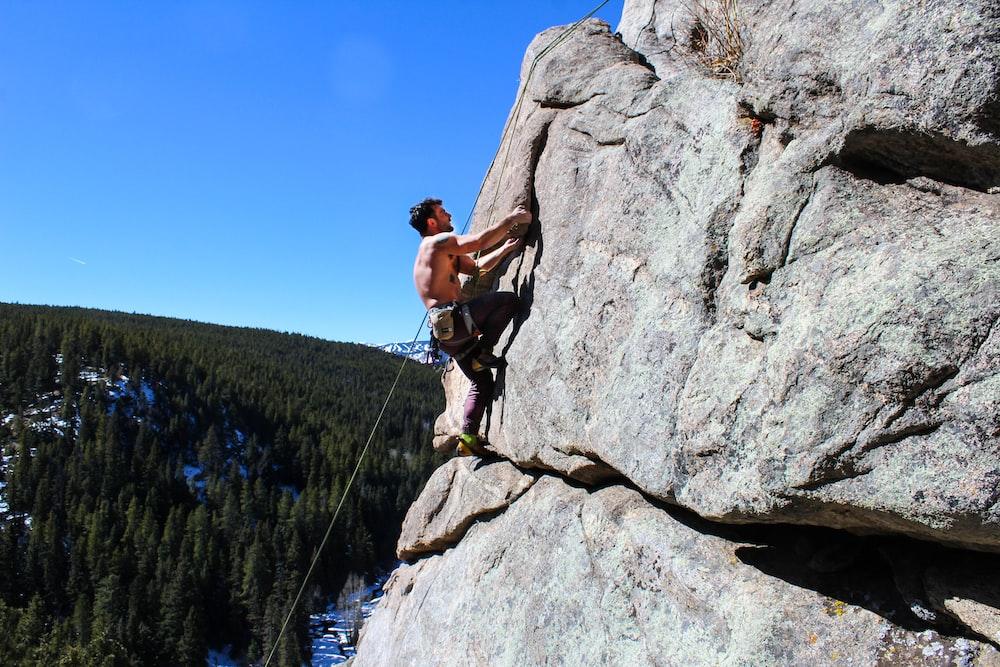 man rockclimbing at daytime