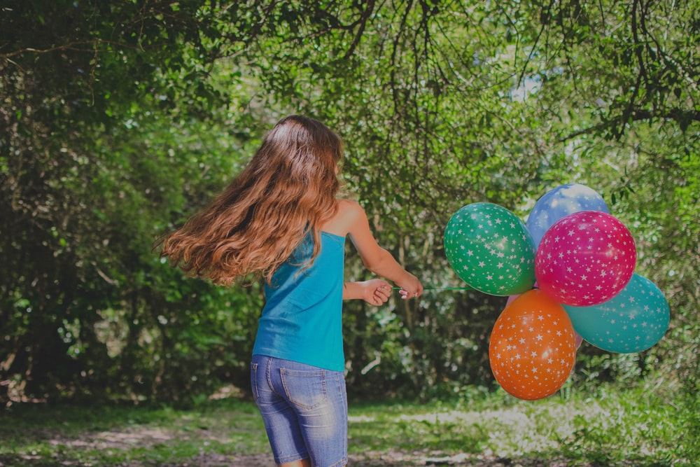 girl in blue top holding balloons
