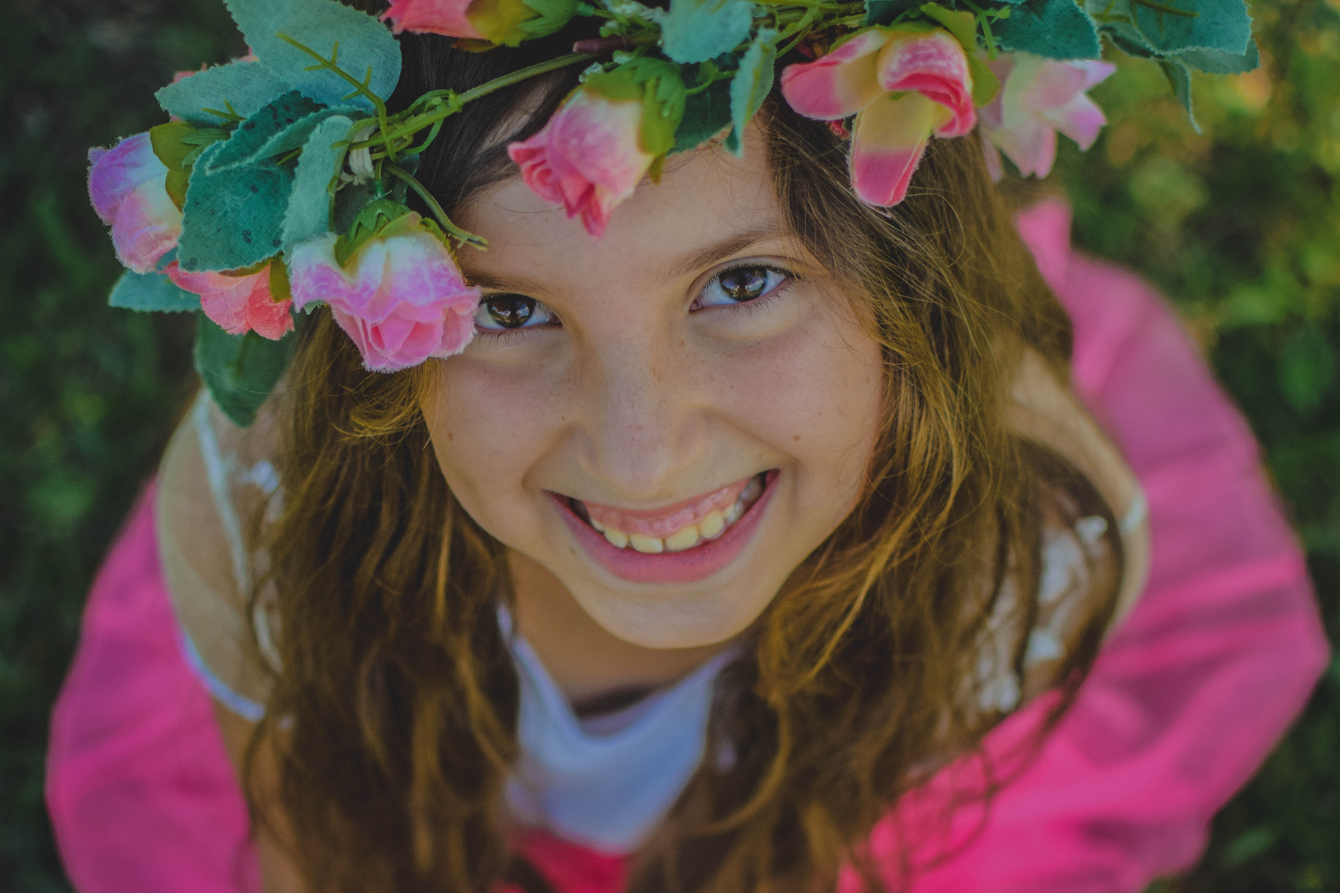 girl wearing flower crown while smiling