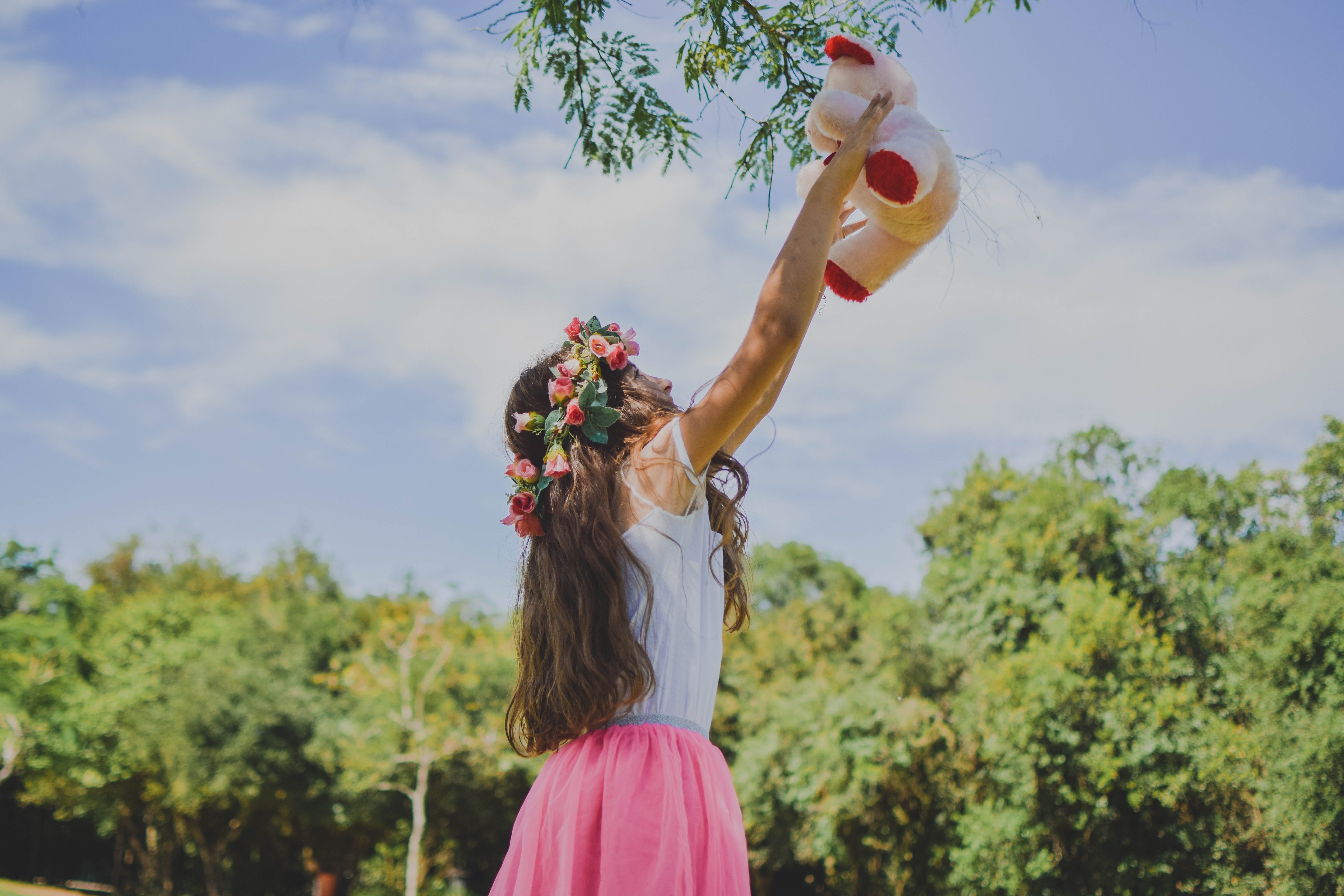 woman in white and pink dress holding bear plush toy