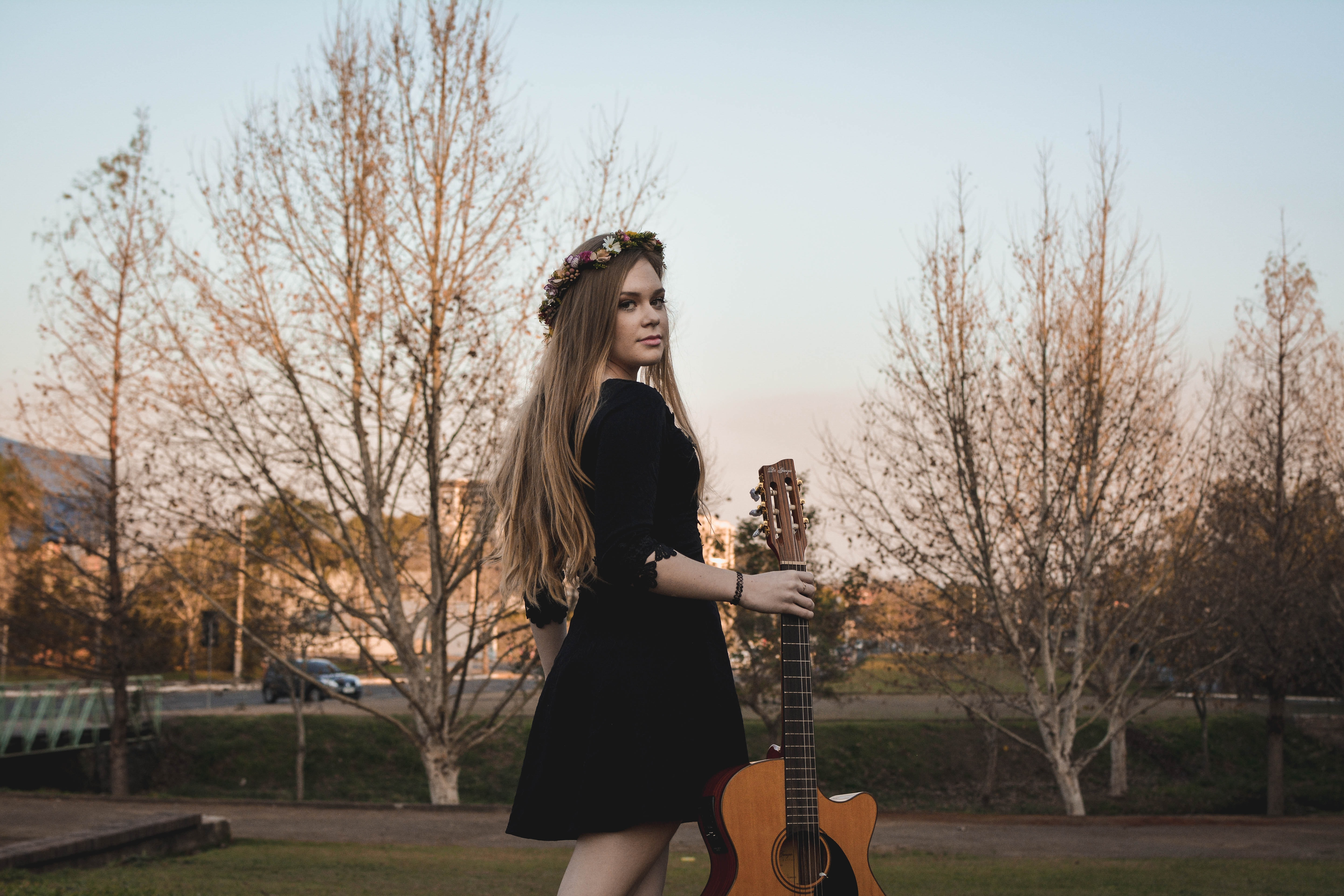 woman standing on lawn while holding classical guitar