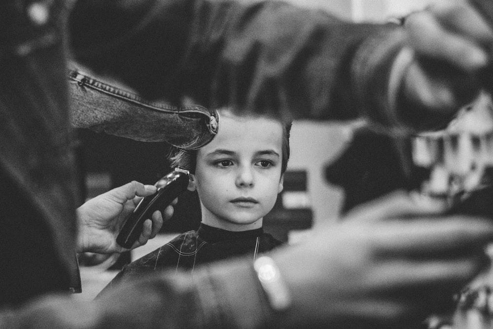 grayscale photo of boy having haircut