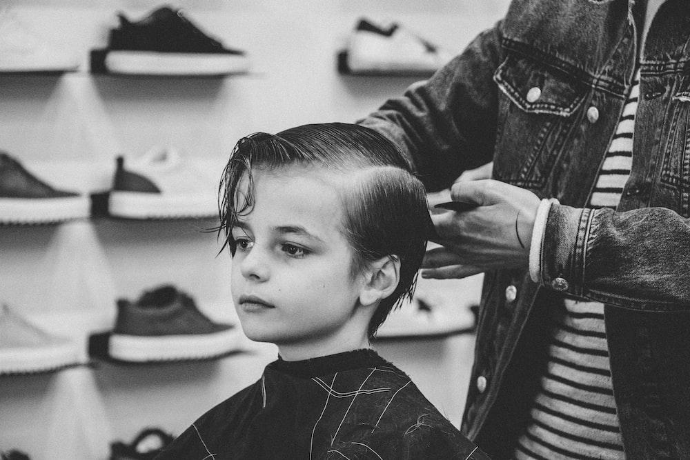 greyscale photo of boy having a haircut