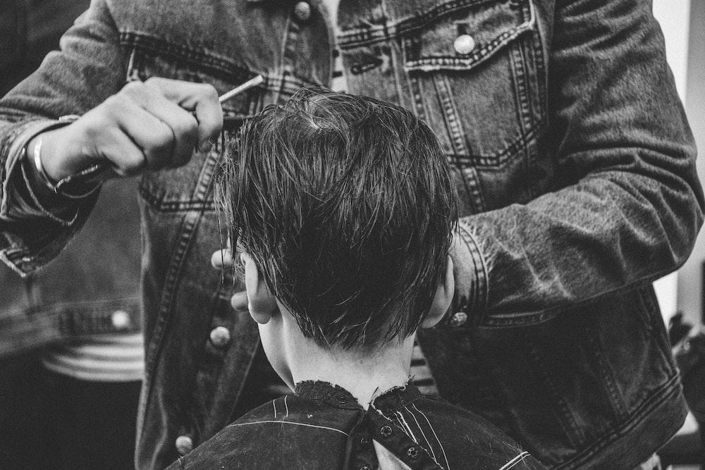 person cutting boy's hair