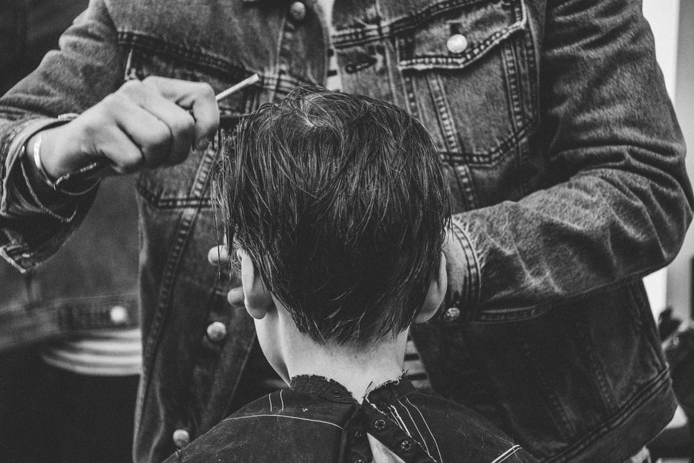 person cutting boy's hair