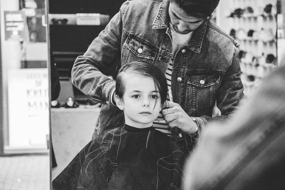 grayscale photography of man holding boys hair