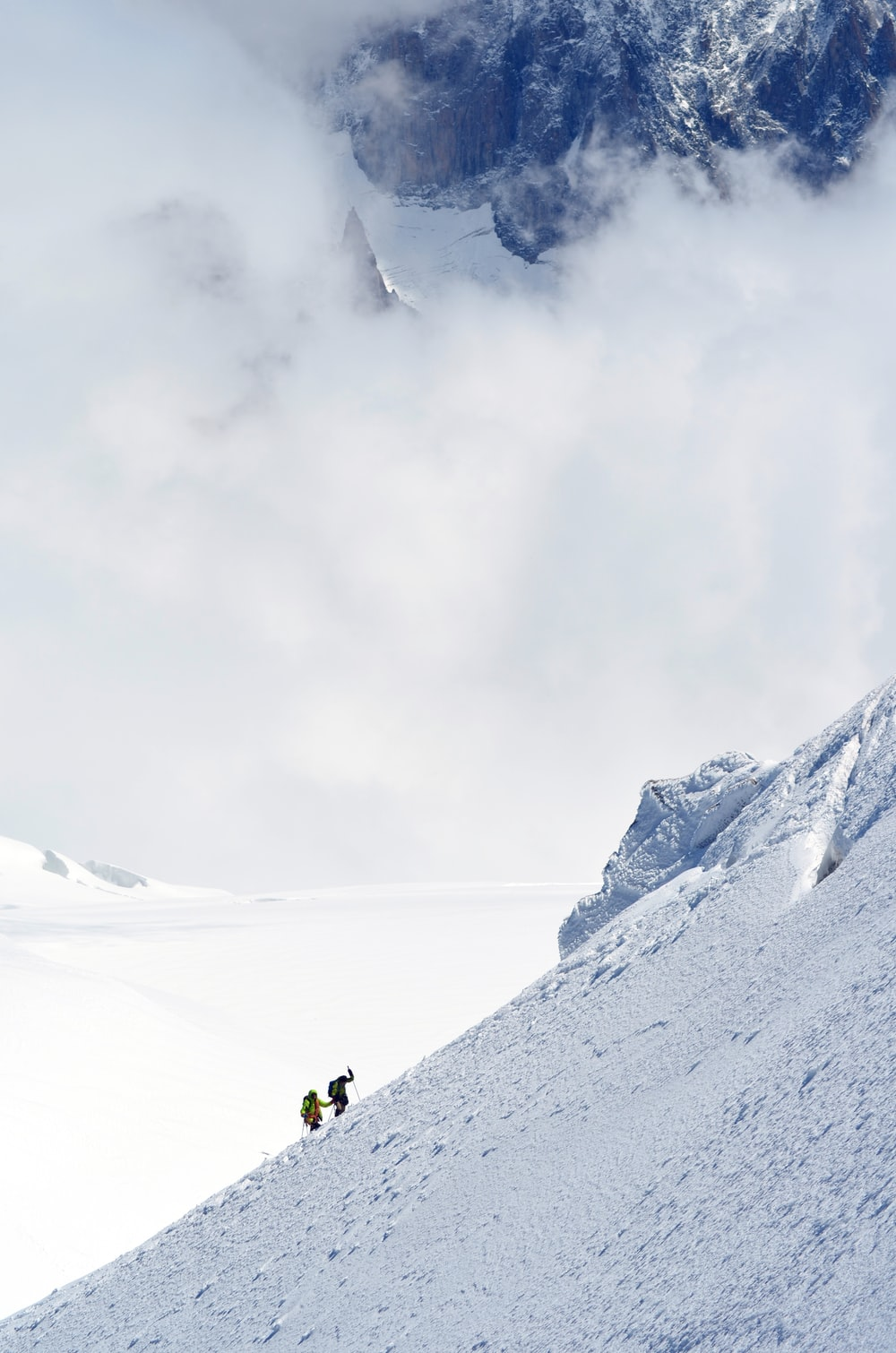 two person hiking on snow-capped mountain