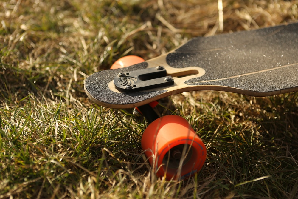 black and brown longboard on green grass at daytime