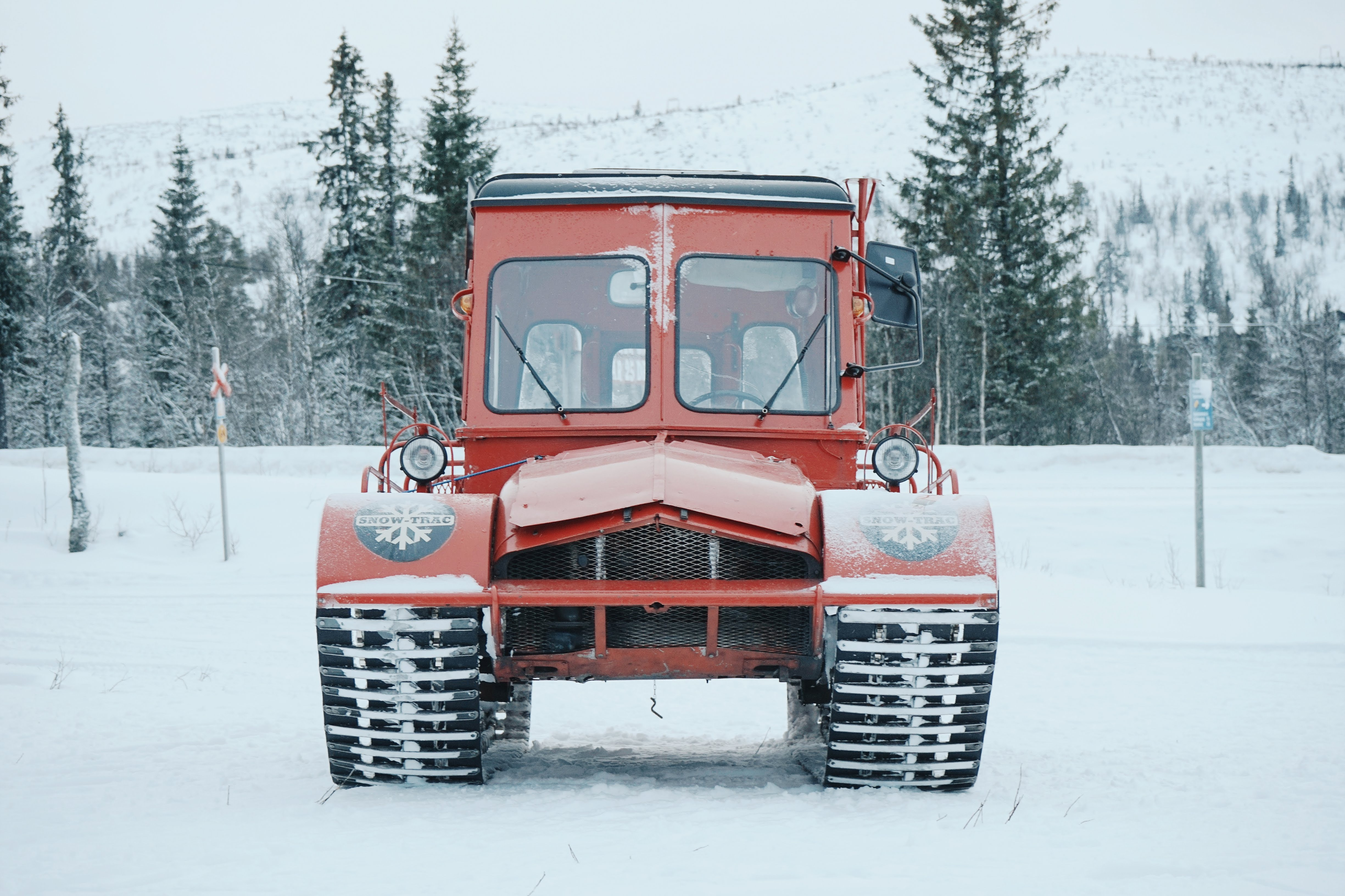 red vehicle passes on road coated snow