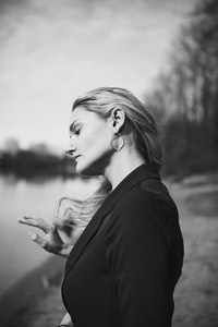 grayscale photo of woman beside body of water