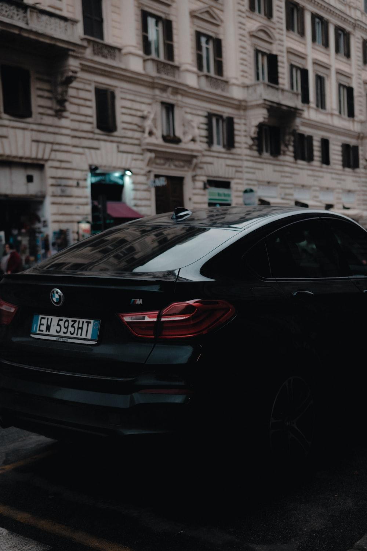 black BMW sedan near beige concrete building
