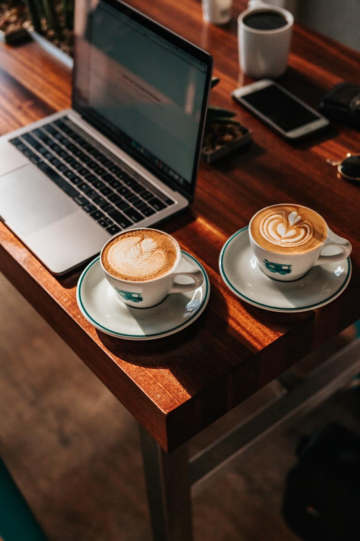 two white ceramic teacups near gray laptop computer