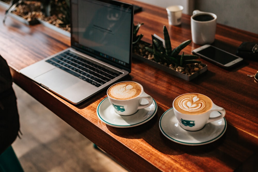two cappuccino served on cups near laptop computer