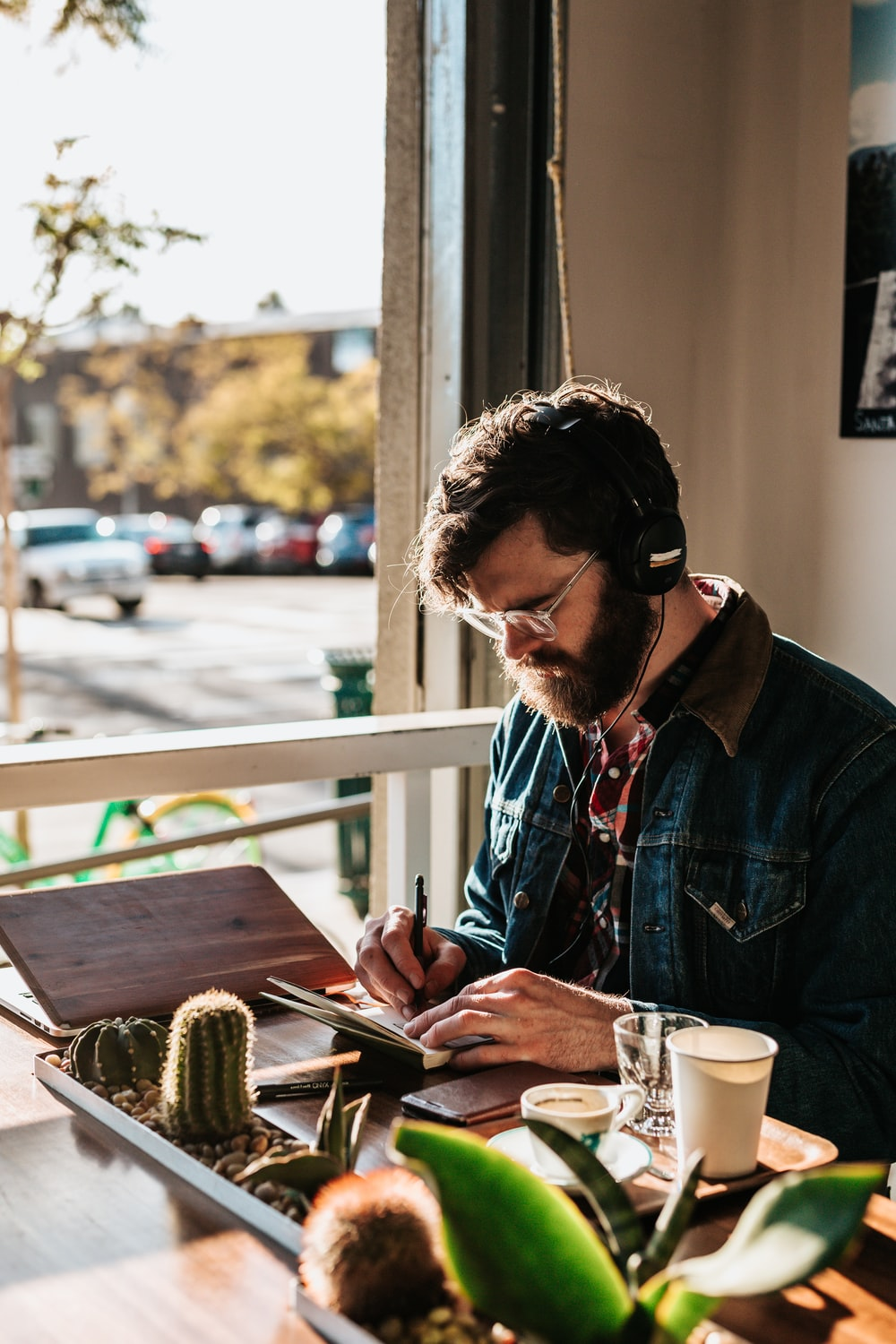man sitting on table in front of table wriing on paper
