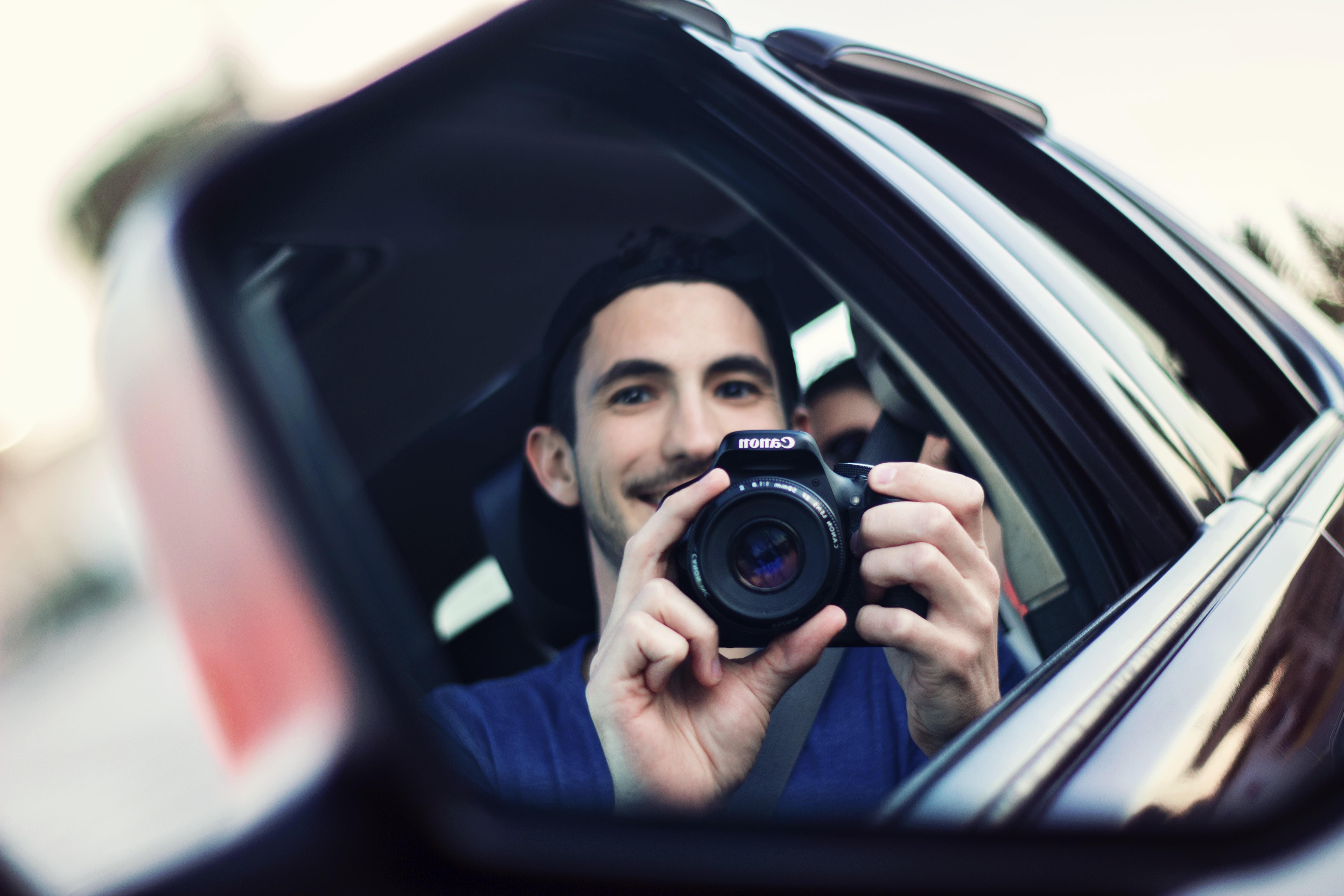 man using black DSLR camera