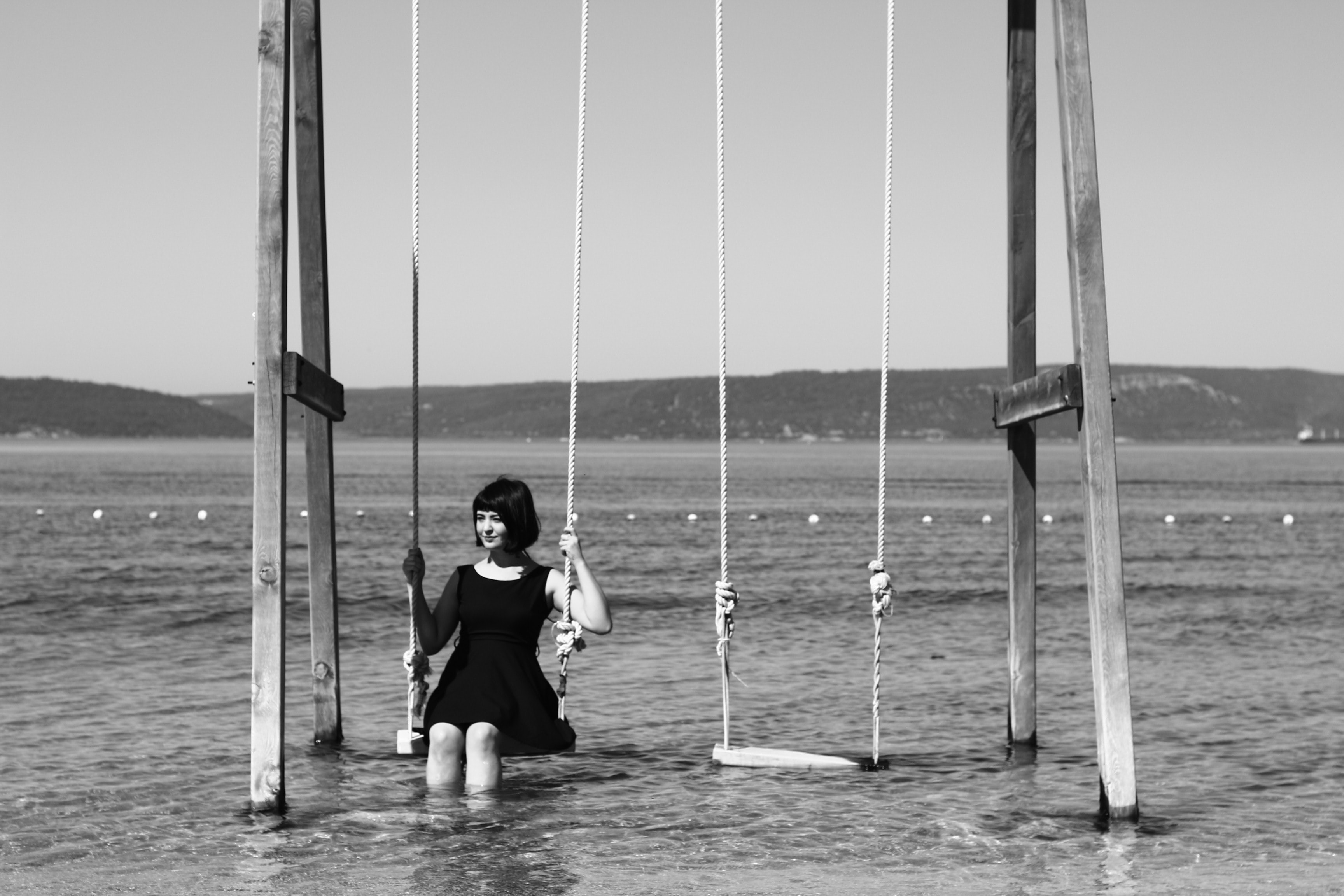 woman sitting on swing in body of water
