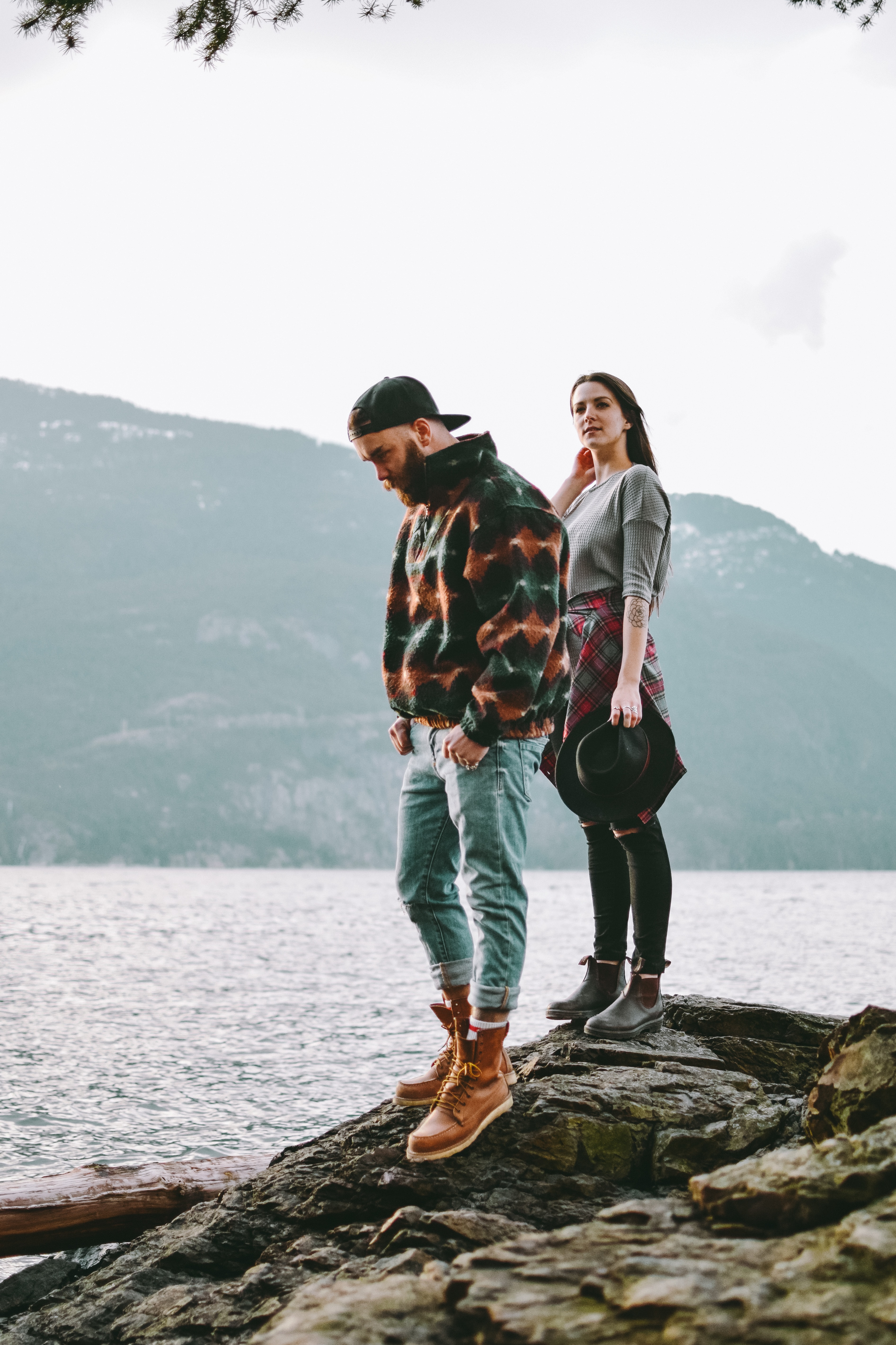 man and woman standing on stone beside beside body of water