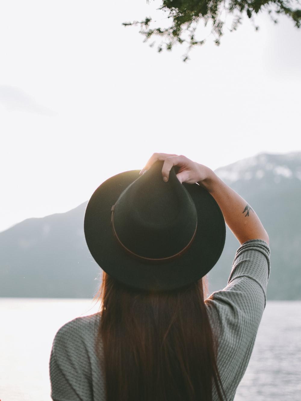 woman wearing black fedora hat near body of water during daytime